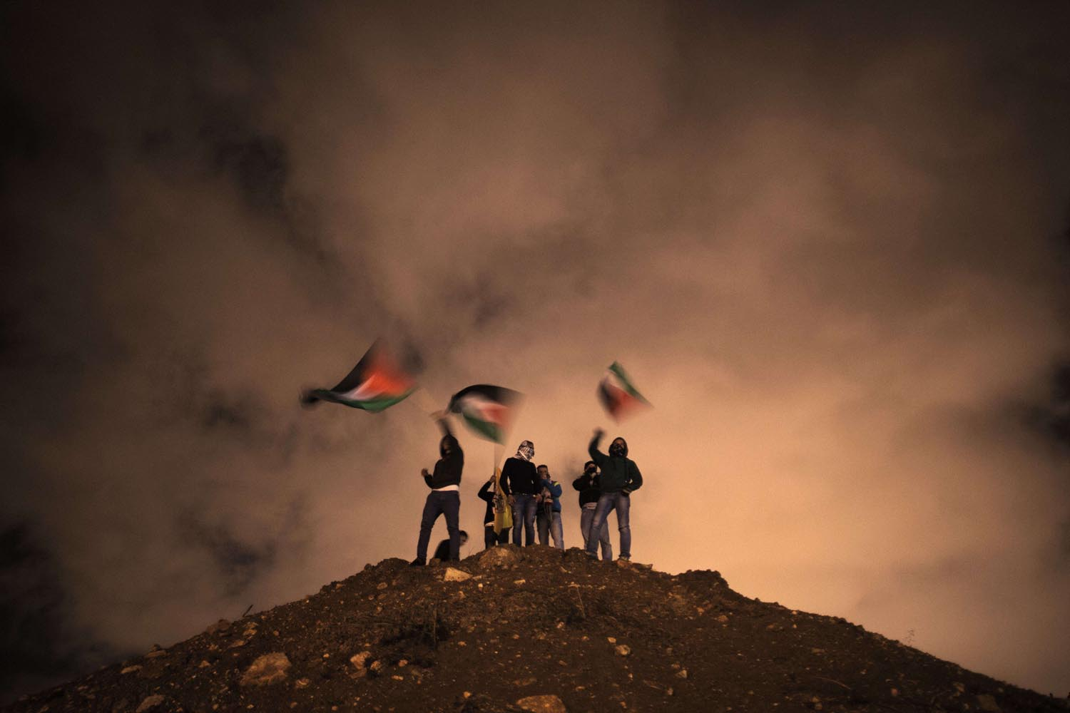 Dec. 31, 2013.                                Palestinians wave their national flag as they await the release of Palestinian prisoners to Jerusalem December 31, 2013. Israel has freed 26 Palestinian prisoners under peace talks brokered by US Secretary of State John Kerry, who returned to the region to boost the faltering negotiations.