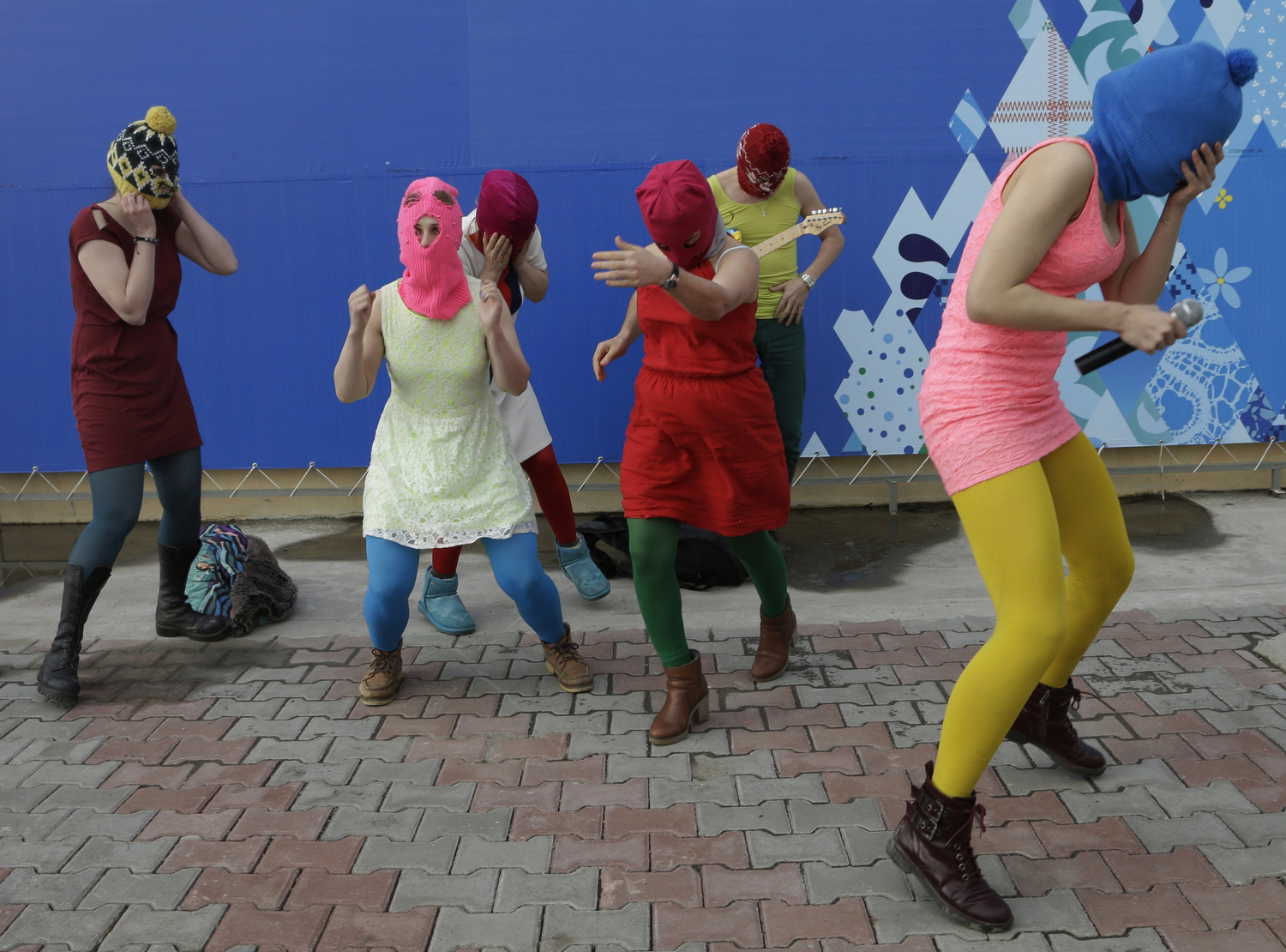 Nadezhda Tolokonnikova covers her face to protect herself from a Cossack militiaman while she and fellow members of the punk group Pussy Riot, including Maria Alekhina, second left, in the pink balaclava, stage a protest performance in Sochi, Russia, on Wednesday, Feb. 19, 2014.