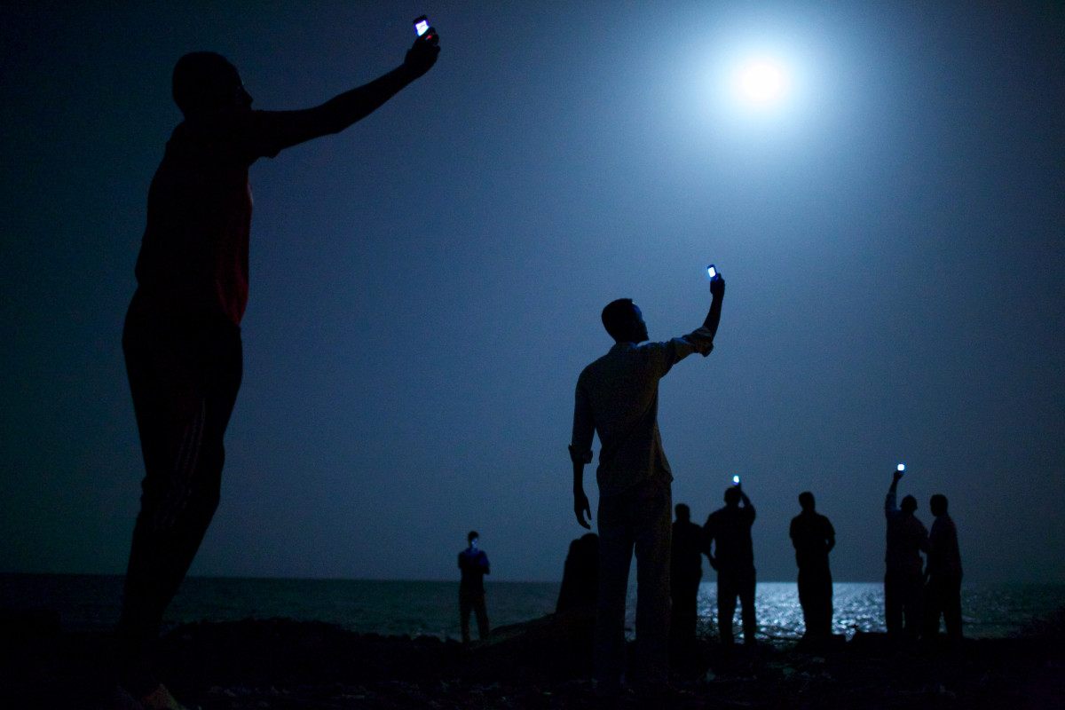 World Press Photo of the Year 2013.                                                                     Feb. 26, 2013. African migrants on the shore of Djibouti city at night, raising their phones in an attempt to capture an inexpensive signal from neighboring Somalia. Djibouti is a common stop-off point for migrants in transit from such countries as Somalia, Ethiopia and Eritrea, seeking a better life in Europe and the Middle East.