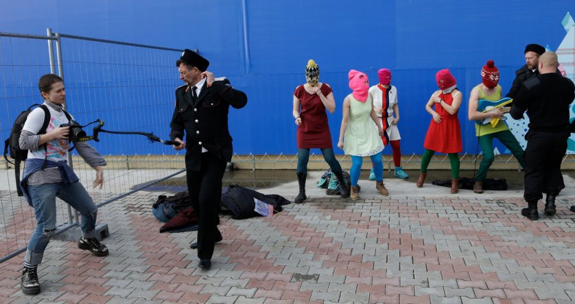 A photographer is whipped by a member of the Cossack militia while trying to photograph members of the punk group Pussy Riot being attacked by Cossack militia and a Russian security officer, in Sochi, Russia, on Wednesday, Feb. 19, 2014.