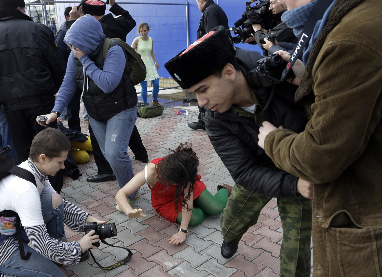 A member of the punk group Pussy Riot lies on the ground as the group are attacked by Cossack militia in Sochi, Russia, on Wednesday, Feb. 19, 2014.