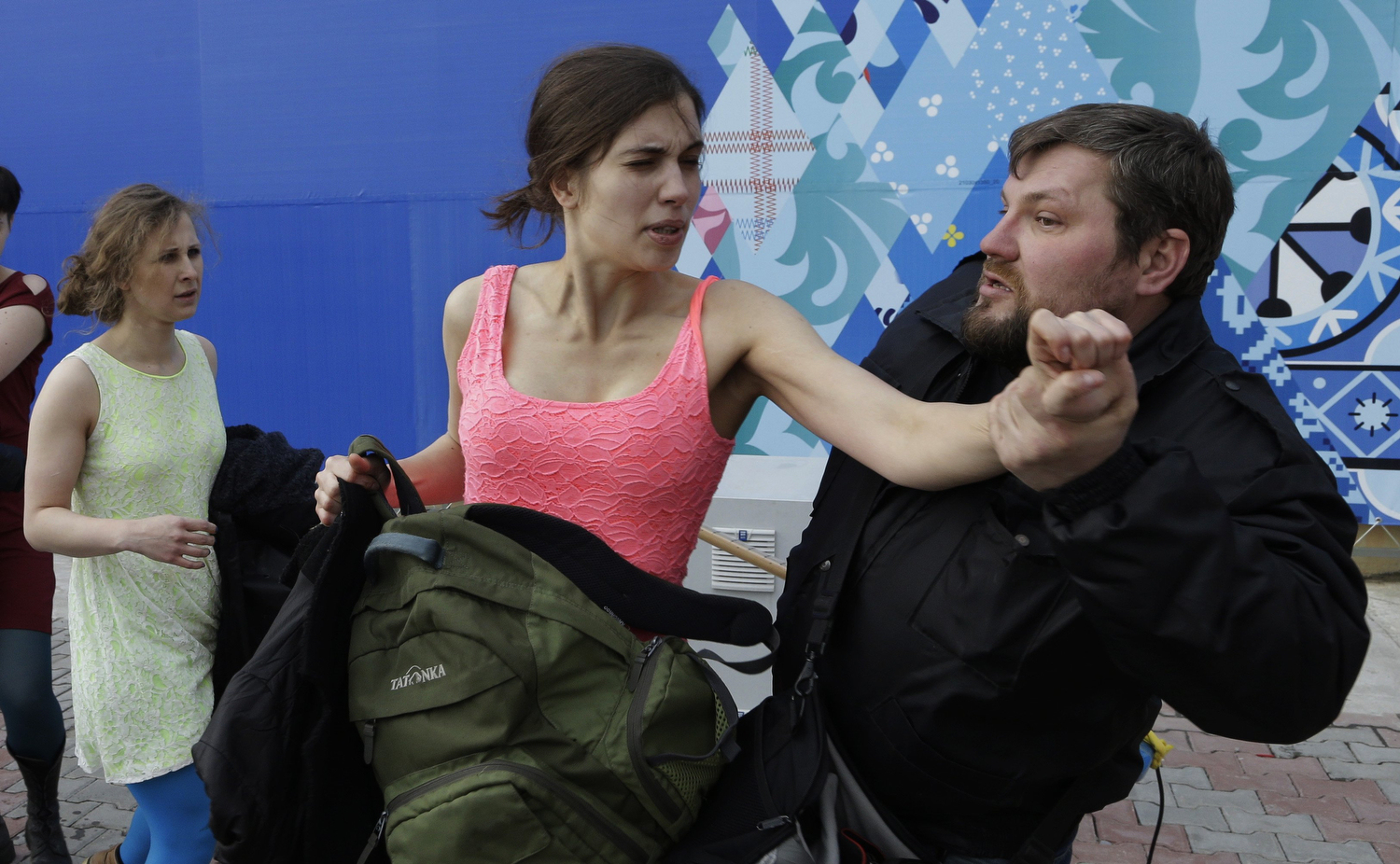 A Russian security officer attacks Nadezhda Tolokonnikova and a photographer as she and fellow members of the punk group Pussy Riot, including Maria Alekhina, left, stage a protest performance in Sochi, Russia, on Wednesday, Feb. 19, 2014.