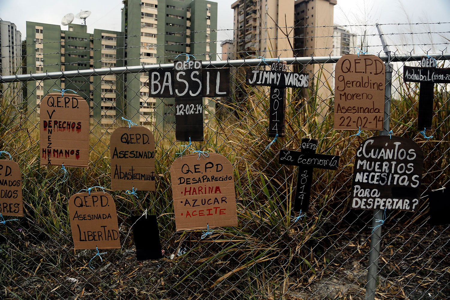 Cardboard cutouts in shapes of headstones and crosses and tied to a fence, bear anti-government protest slogans and names of those who have died in recent protests, in Caracas, March 5, 2014.