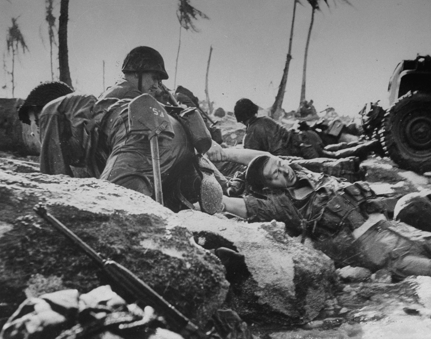 Caption from LIFE.  On the coral beach of Eniwetok's Engebi Island, a Marine drags a dead comrade out of the surf.  See write-up below for a discussion of this photograph.