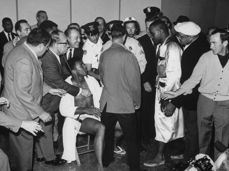 Sonny Liston at the weighting-in ceremonies before his heavyweight championship fight with Cassius Clay (sitting at left).