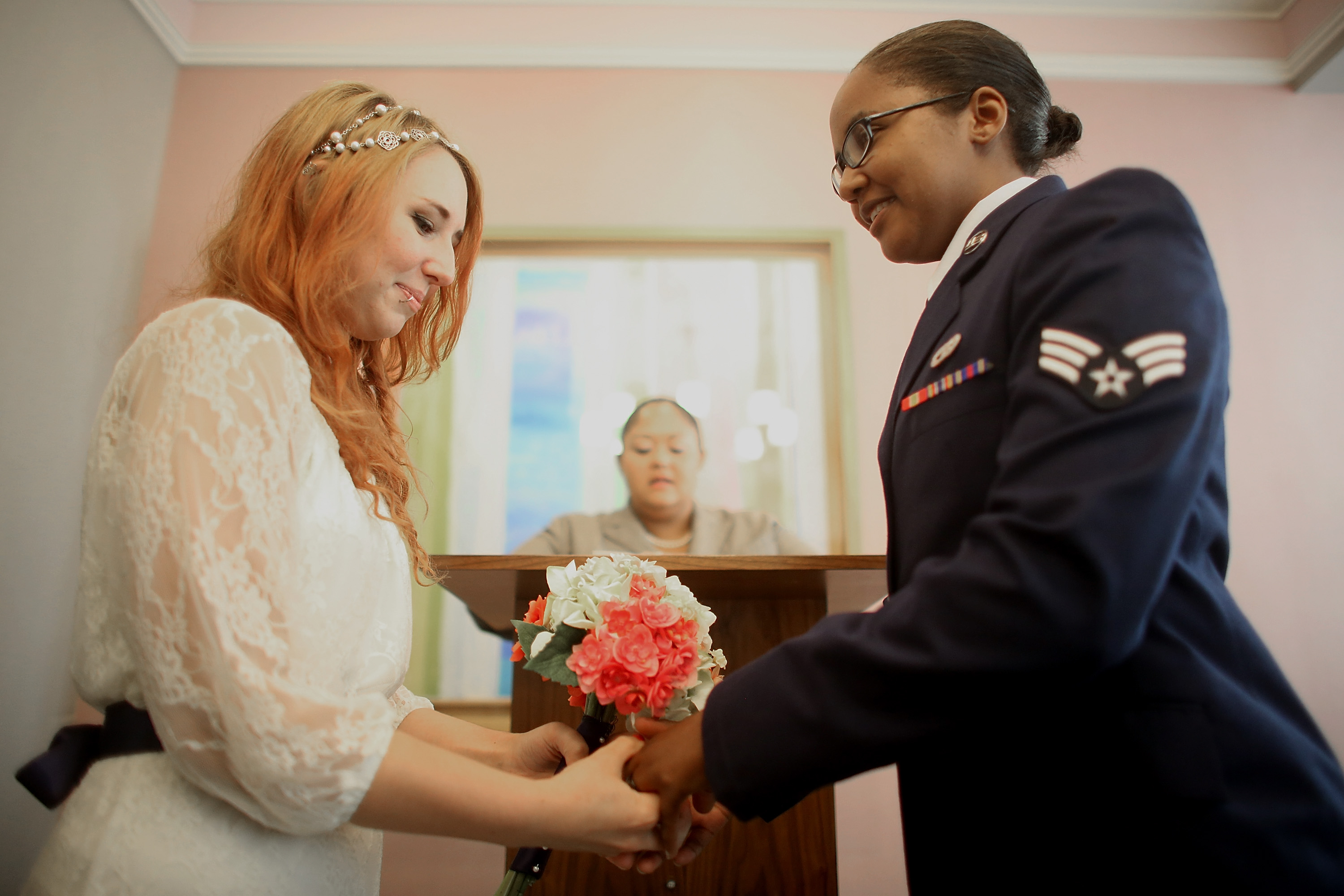 U.S. Air Force Senior Airman Shyla Smith (R) and Courtney Burdeshaw hold hands in the west chapel during their wedding ceremony at the Manhattan Marriage Bureau the day after the U.S. Supreme Court ruling on DOMA on June 27, 2013