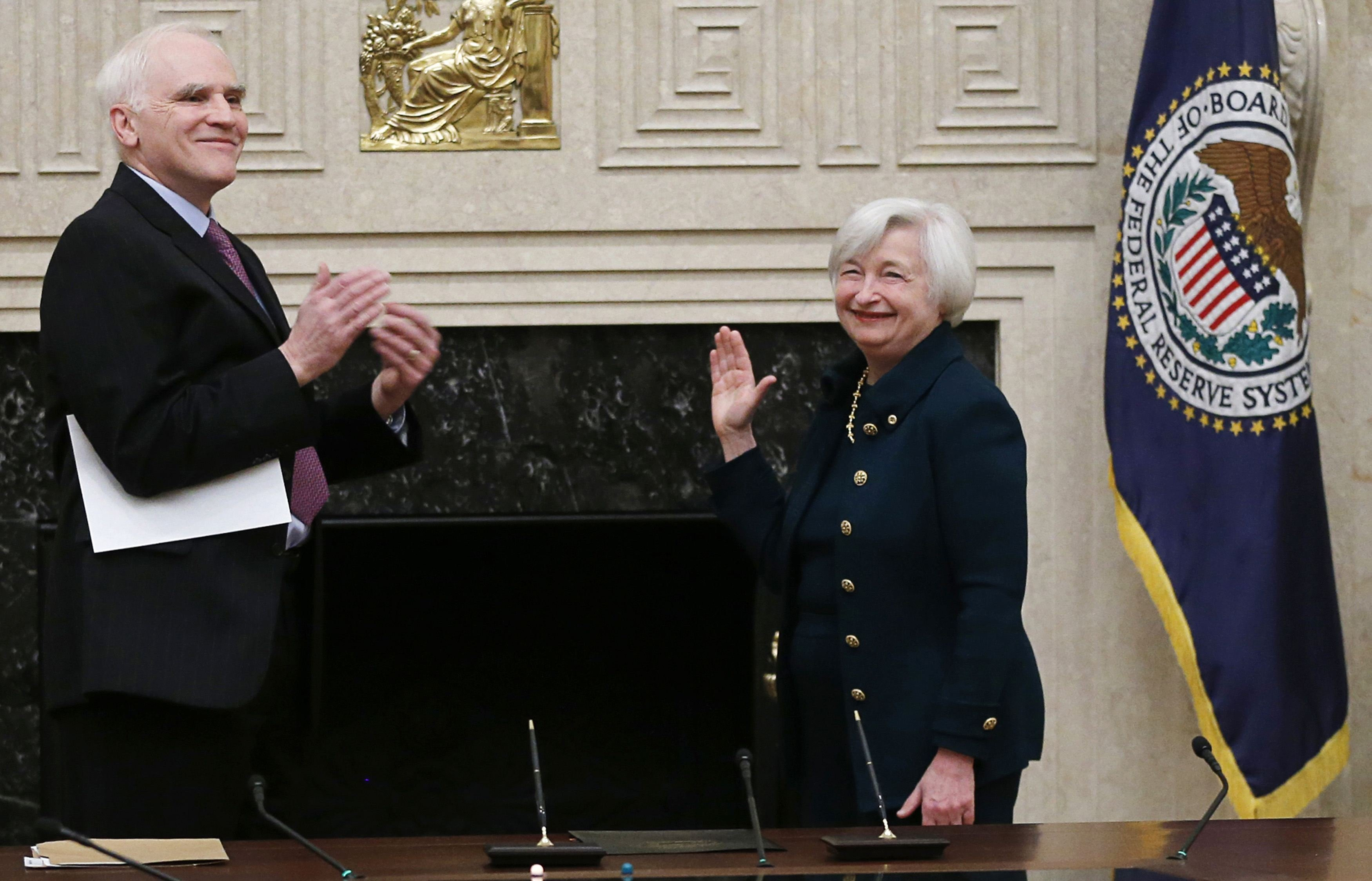 Federal Reserve Board Governor Daniel Tarullo (L) applauds new Federal Reserve Board Chairwoman Janet Yellen after administering the oath of office to Yellen at the Federal Reserve Board in Washington February 3, 2014.