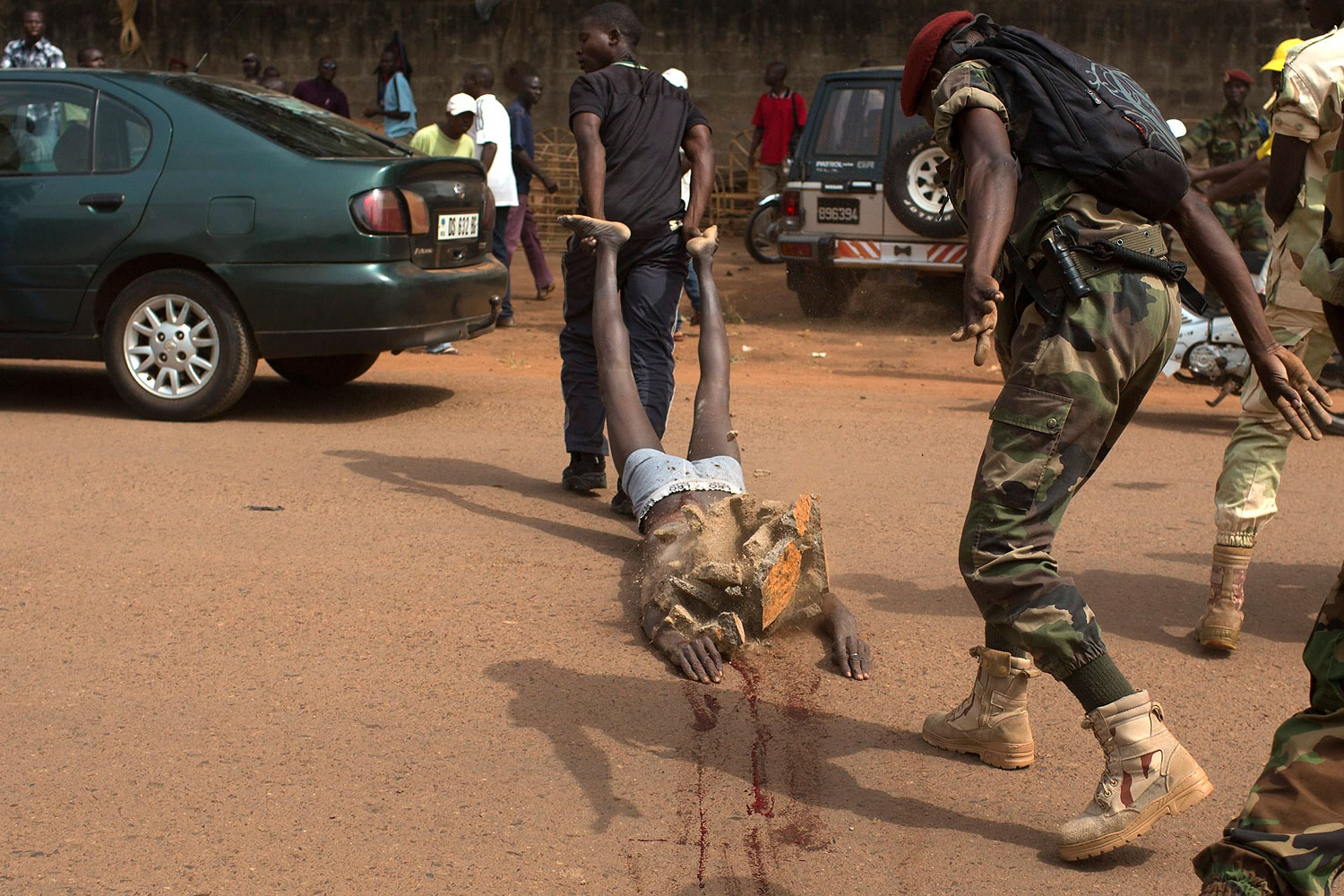A man uses rock to strike the corpse of a man, who was killed as he was accused of joining the ousted Seleka fighters, in the capital Bangui, Feb. 5, 2014.