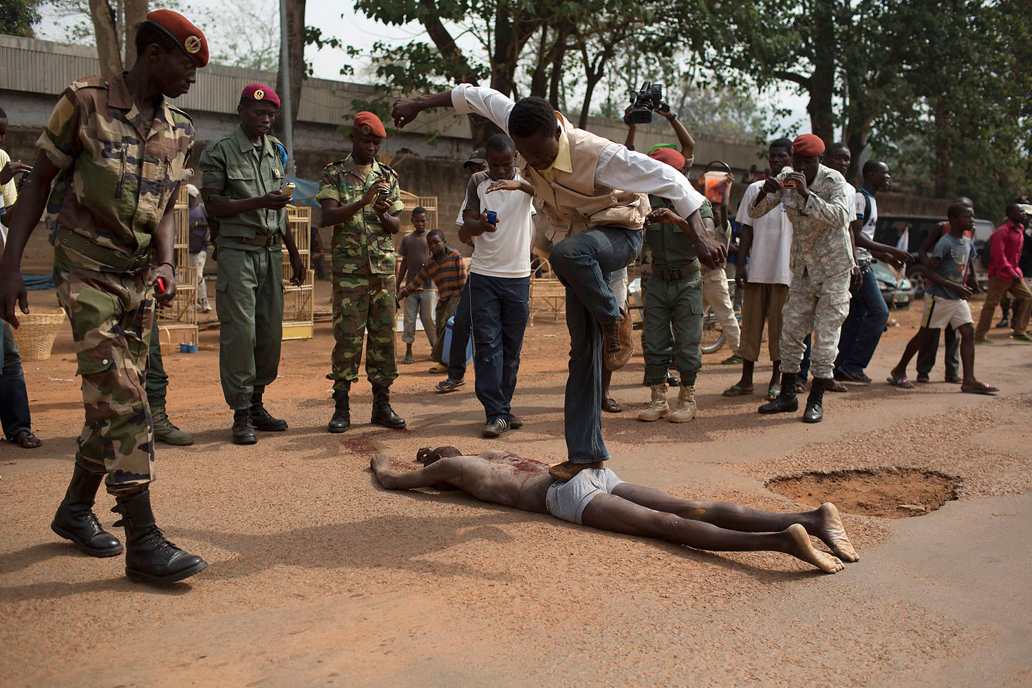 A man jumps on the corpse of a man, who was killed as he was accused of joining the ousted Seleka fighters, in the capital Bangui, Feb. 5, 2014.