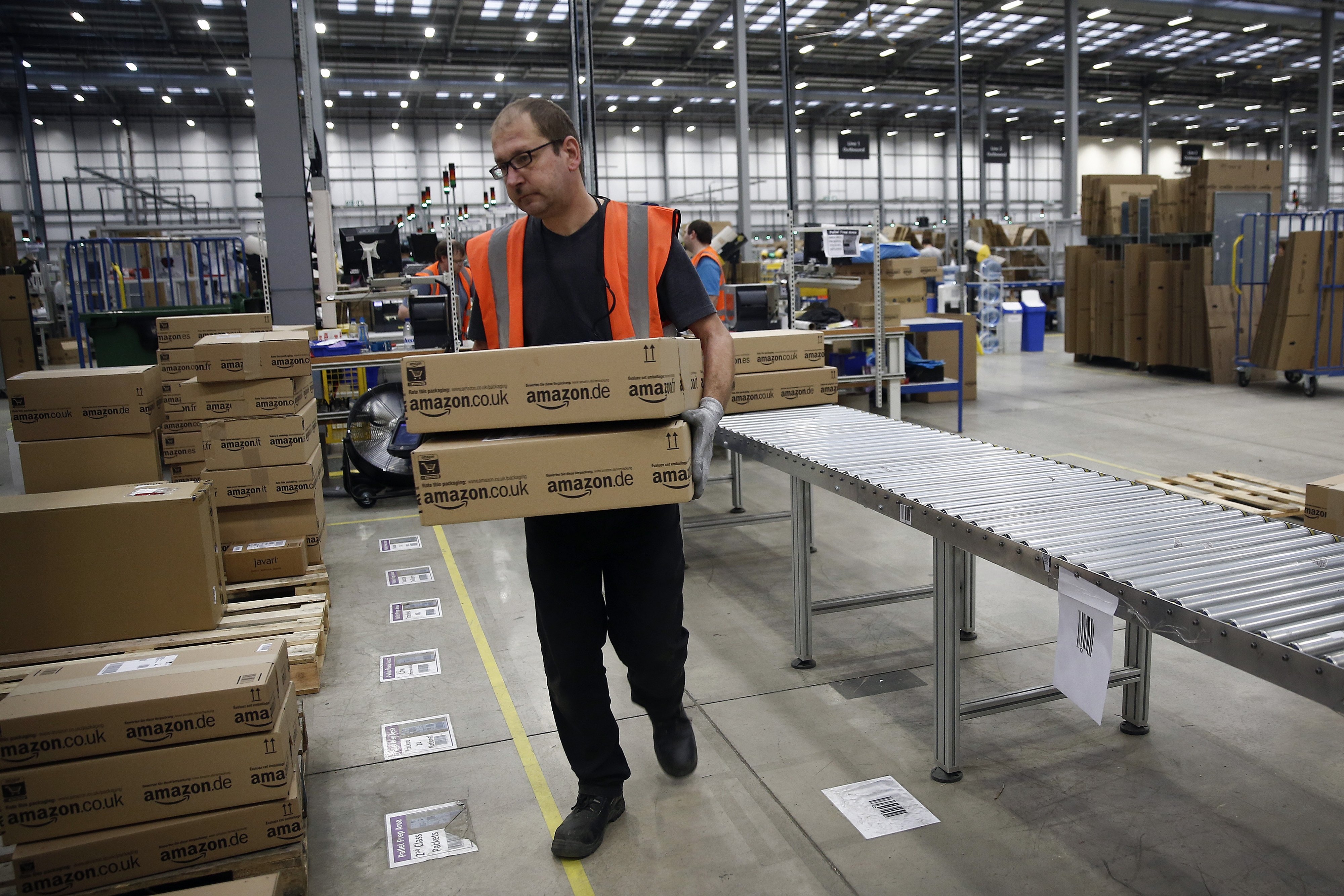 A employee sorts packaged customer orders ahead of shipping at one of Amazon.com Inc.'s fulfillment centers.