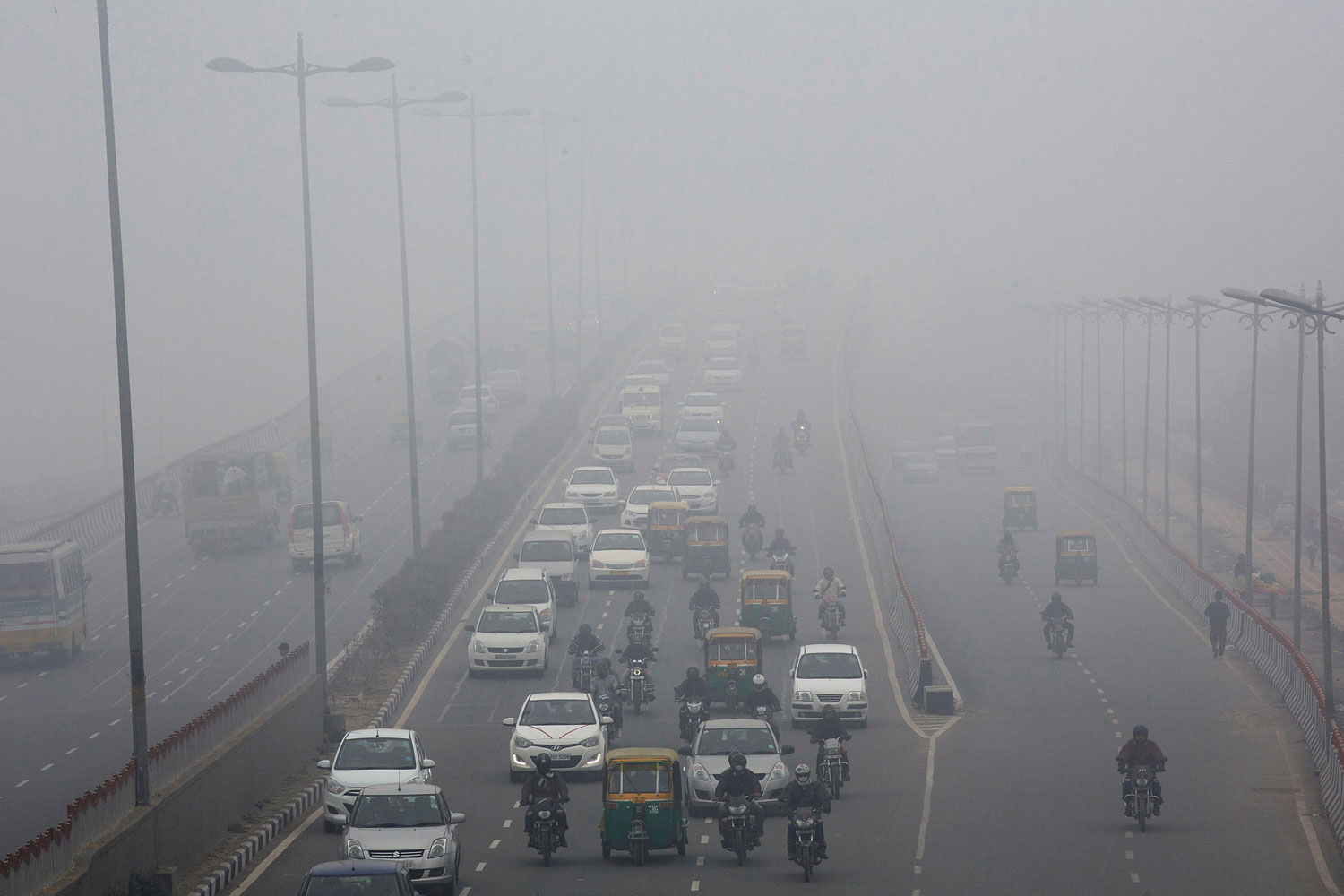 Traffic make way in haze mainly caused by air pollution in Delhi on Jan. 20, 2014