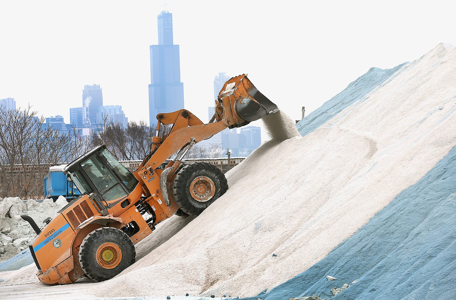 A Streets and Sanitation worker grooms a pile of road salt as the city makes preparations for another winter storm on Feb. 4, 2014 in Chicago.