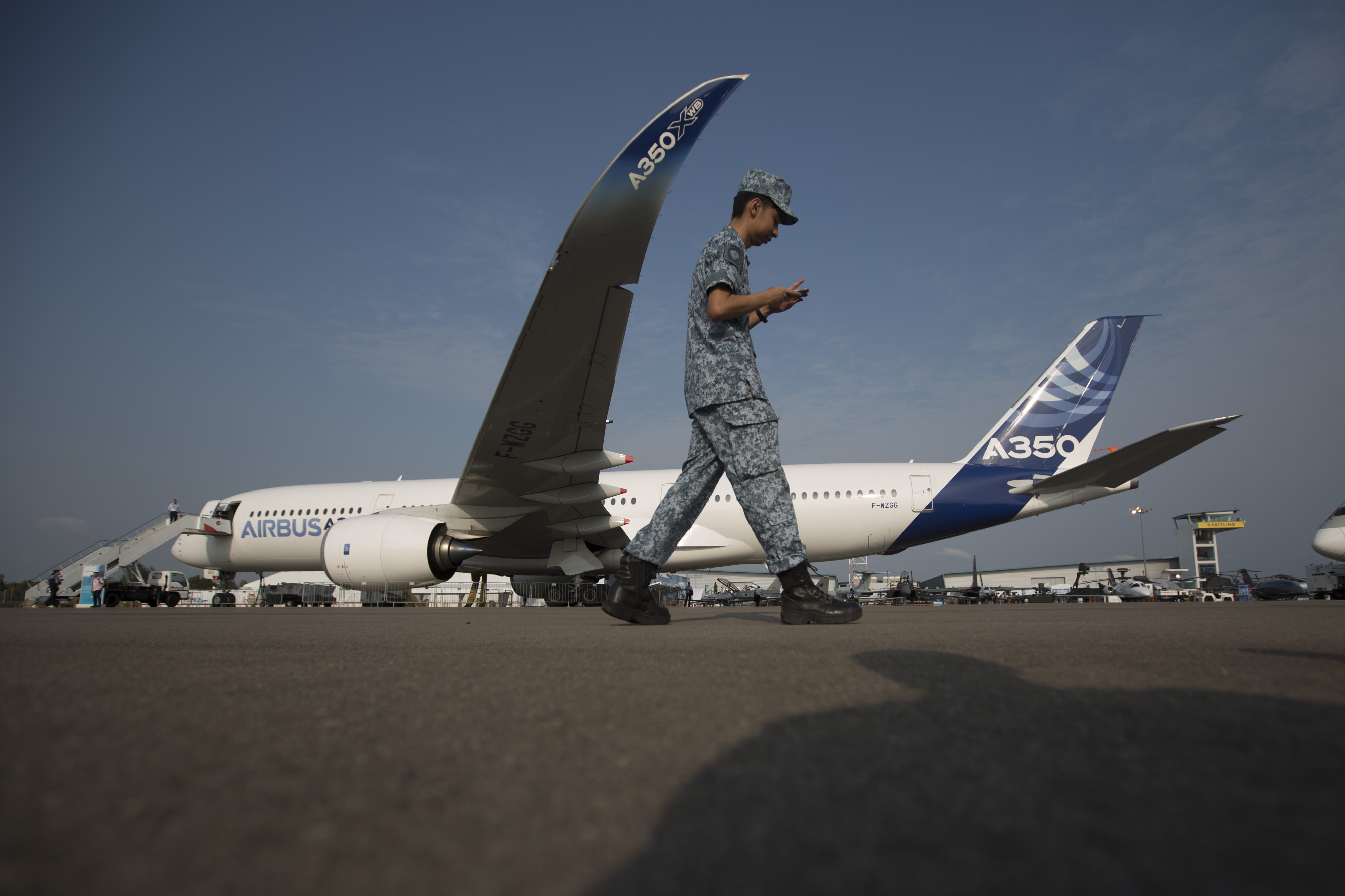 A soldier walks past an Airbus SAS A350 XWB flight test aircraft (MSN3) displayed at the Singapore Airshow held at the Changi Exhibition Centre in Singapore, on Feb. 11, 2014.
