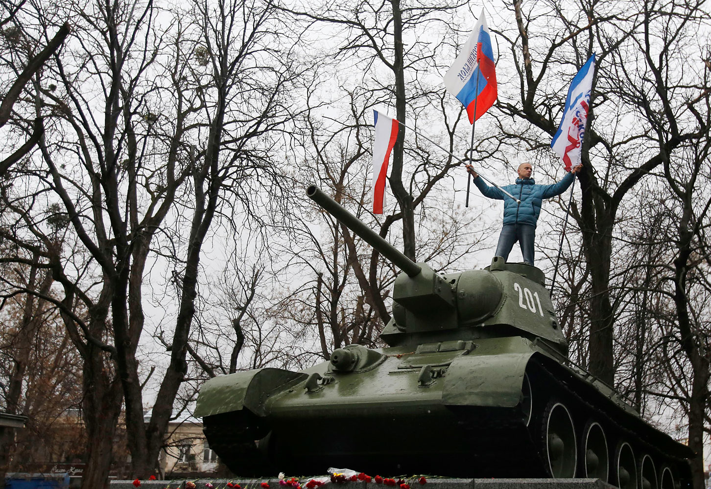 A Pro-Russian demonstrator waves Russian and Crimea flags atop an old Soviet Army tank during a protest in front of a local government building in Simferopol, Crimea, Ukraine, Feb. 27, 2014.