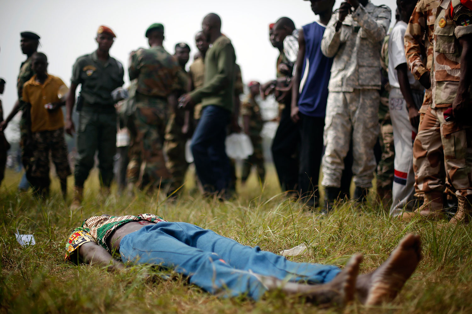 A man suspected to be a Muslim Seleka militiaman lays wounded after being stabbed by newly enlisted Central African Armed Forces soldiers moments after Central African Republic Interim President Catherine Samba-Panza addressed the troops in Bangui, Feb. 5, 2014.
