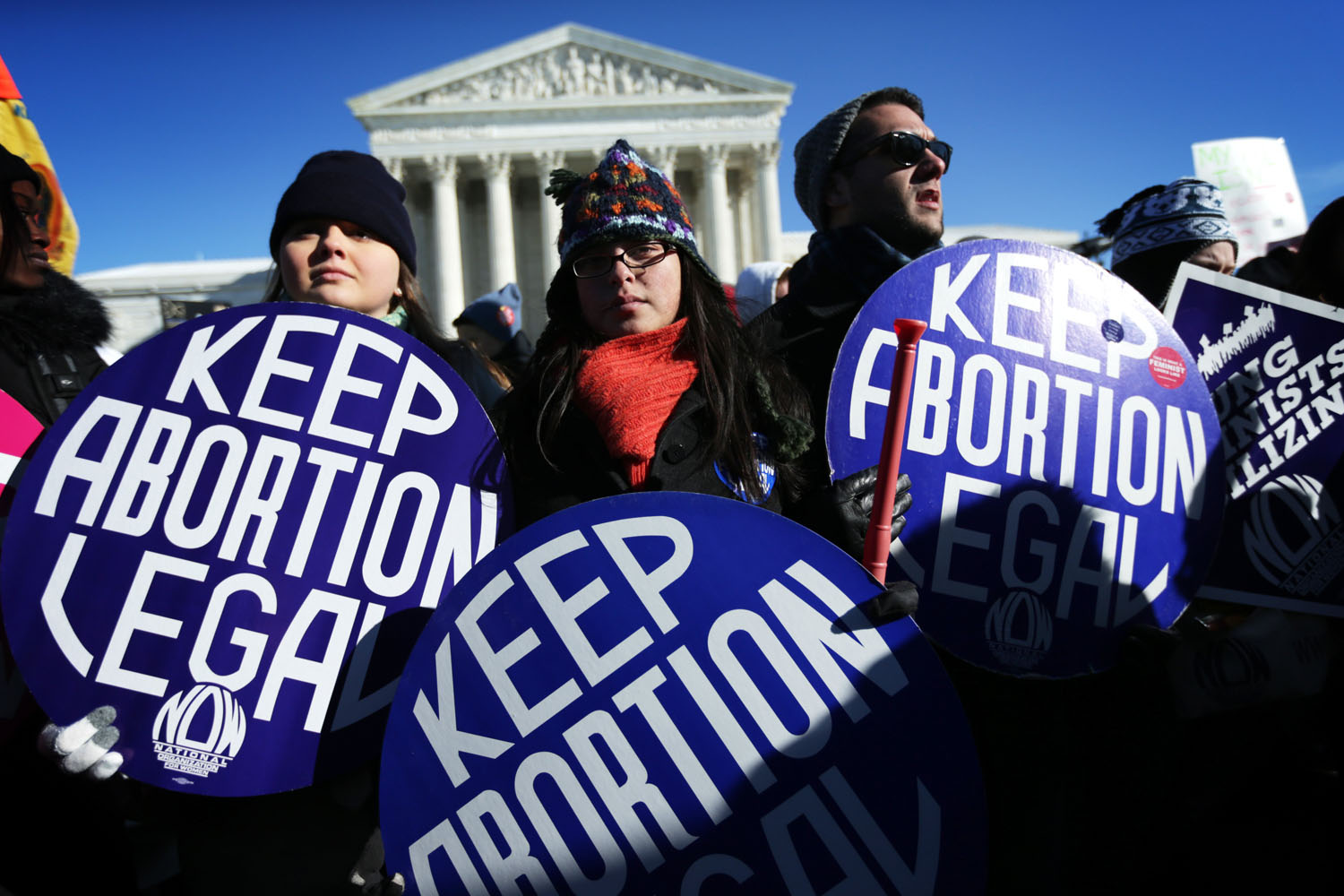 Pro-choice activists hold signs as marchers of the annual March for Life arrive in front of the U.S. Supreme Court Jan. 22, 2014 on Capitol Hill in Washington, D.C.