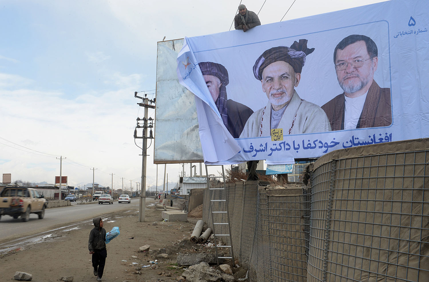 Afghan workers install an election campaign poster of Afghan presidential candidate Ashraf Ghani Ahmadzai in Kabul on Feb. 3, 2014.