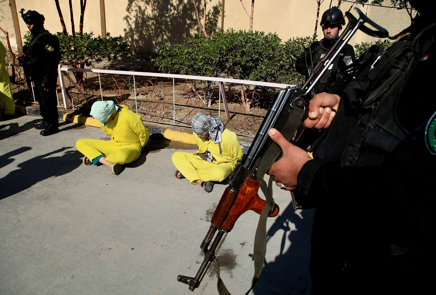 Members of Iraq's Special Weapons and Tactics Team stand guard as blindfolded suspected members of the al-Qaida-linked ISIS are displayed at the federal police headquarters in Basra, Feb 11, 2014.