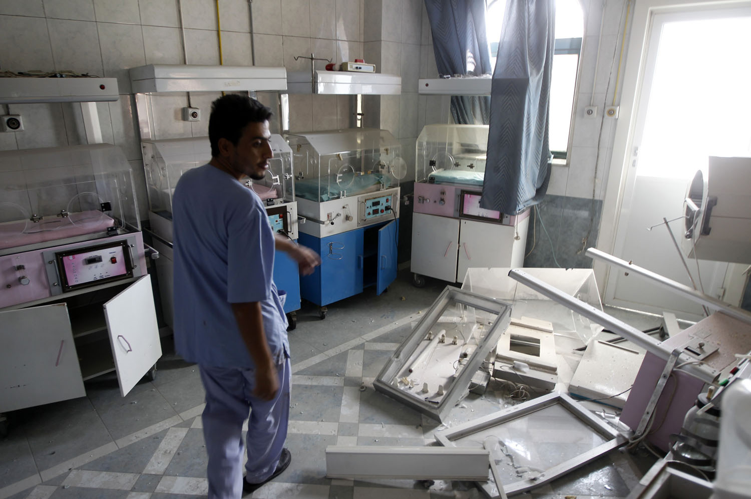 A man walks through a room at Dar Al Shifa Hospital, damaged in a Syrian Air force air strike the day before, in the Sha'aar neighborhood of Aleppo on Aug. 15, 2012.