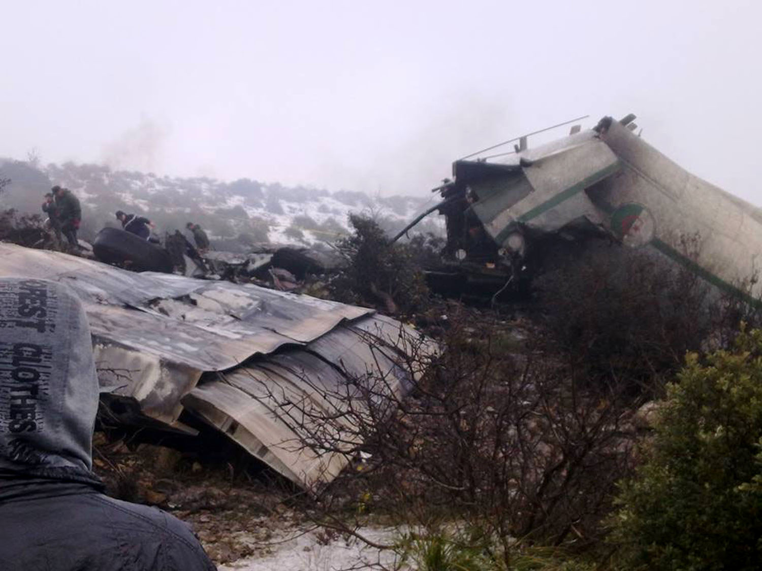 A man watches rescue workers working at the wreckage of Algerian military transport aircraft after it slammed into a mountain in the country's rugged eastern region, Feb. 11, 2014. A civil defense official said 102 people on board were killed but one person managed to survive. The U.S.-built C-130 Hercules transport crashed about noon near the town of Ain Kercha, 50 kilometers (30 miles) southeast of Constantine, the main city in eastern Algeria.