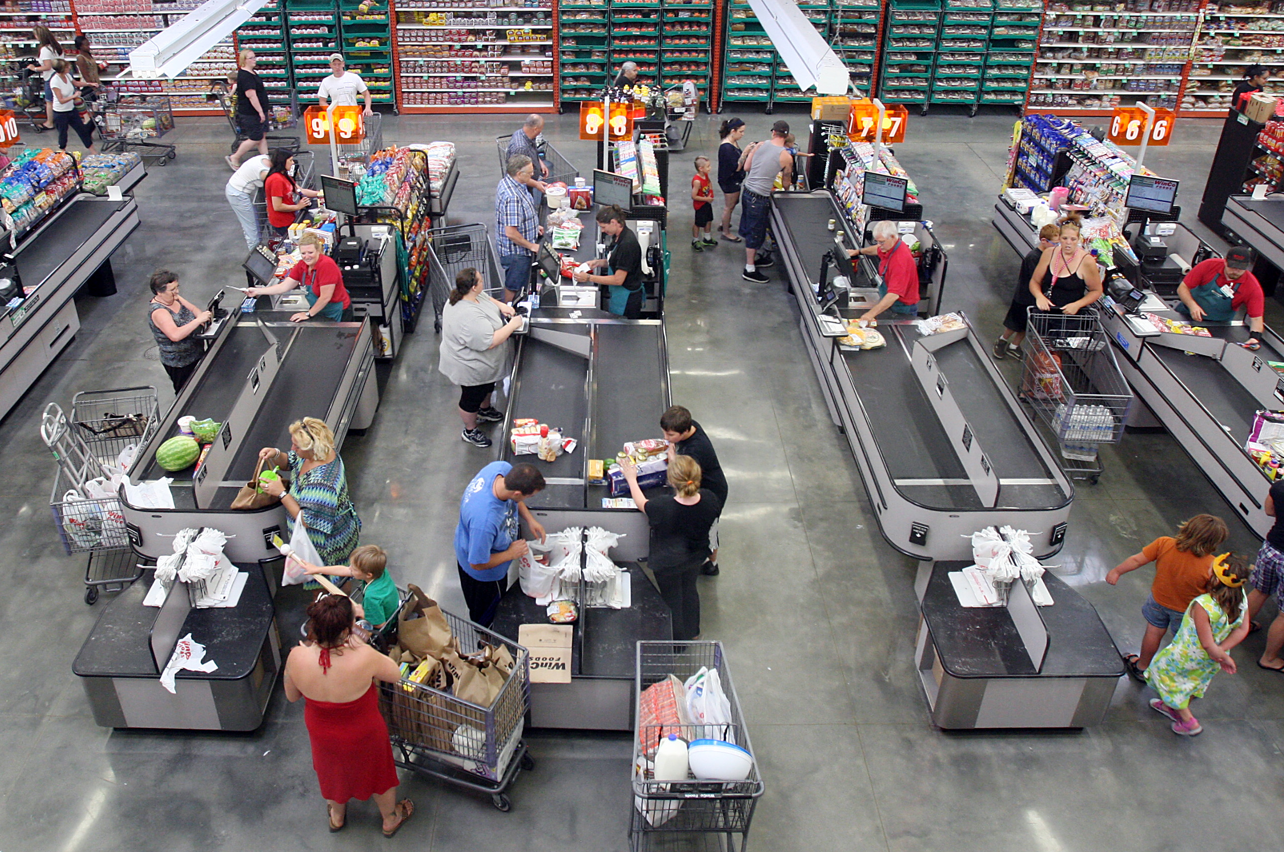 Customers bag their own groceries at checkout counters at WinCo Foods on Fairview Avenue in Boise, Idaho, on July 1, 2013