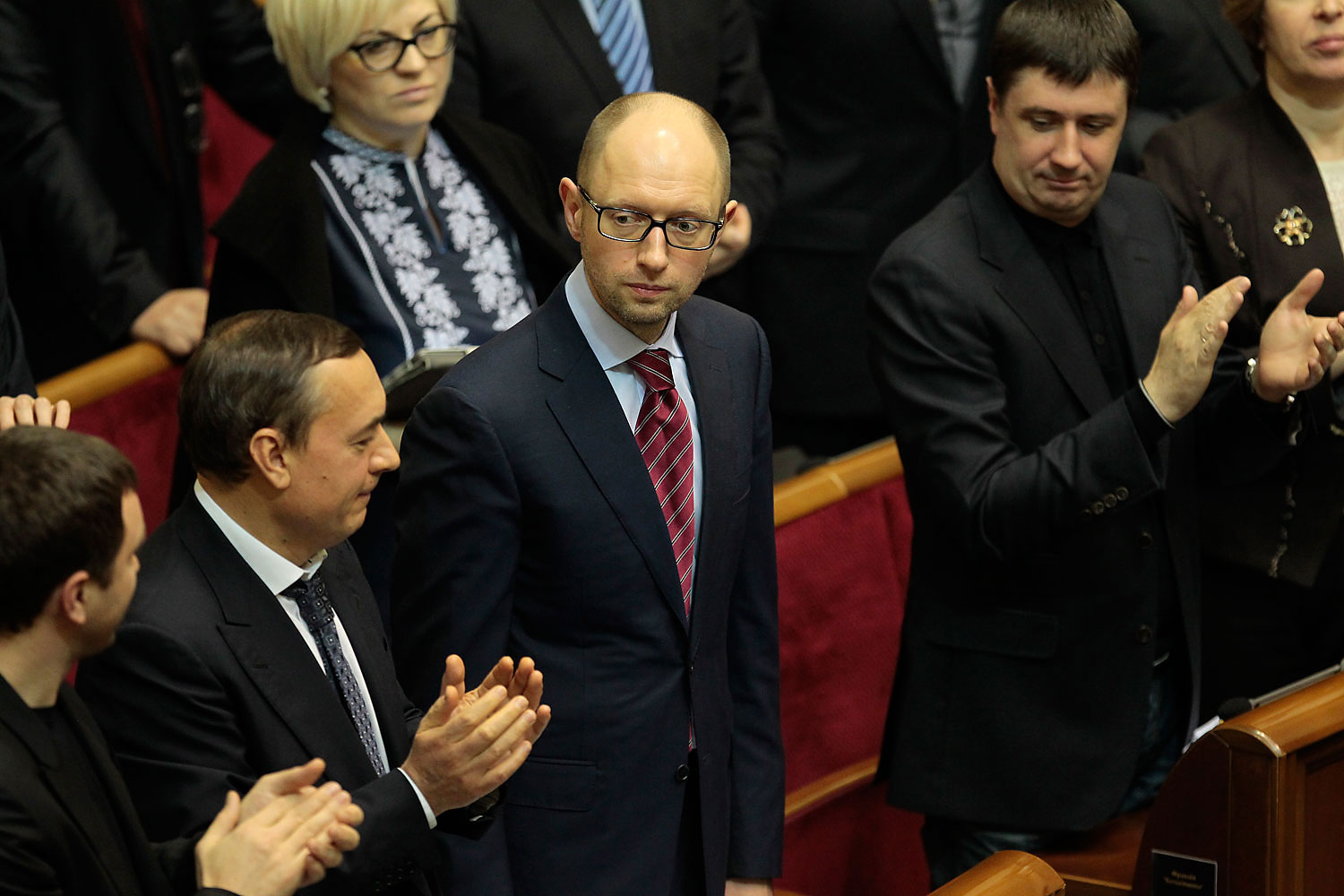 Ukrainian lawmakers applaud new Prime Minister Arseniy Yatsenyuk, center, during a session at the Ukrainian parliament in Kiev, Feb. 27, 2014.