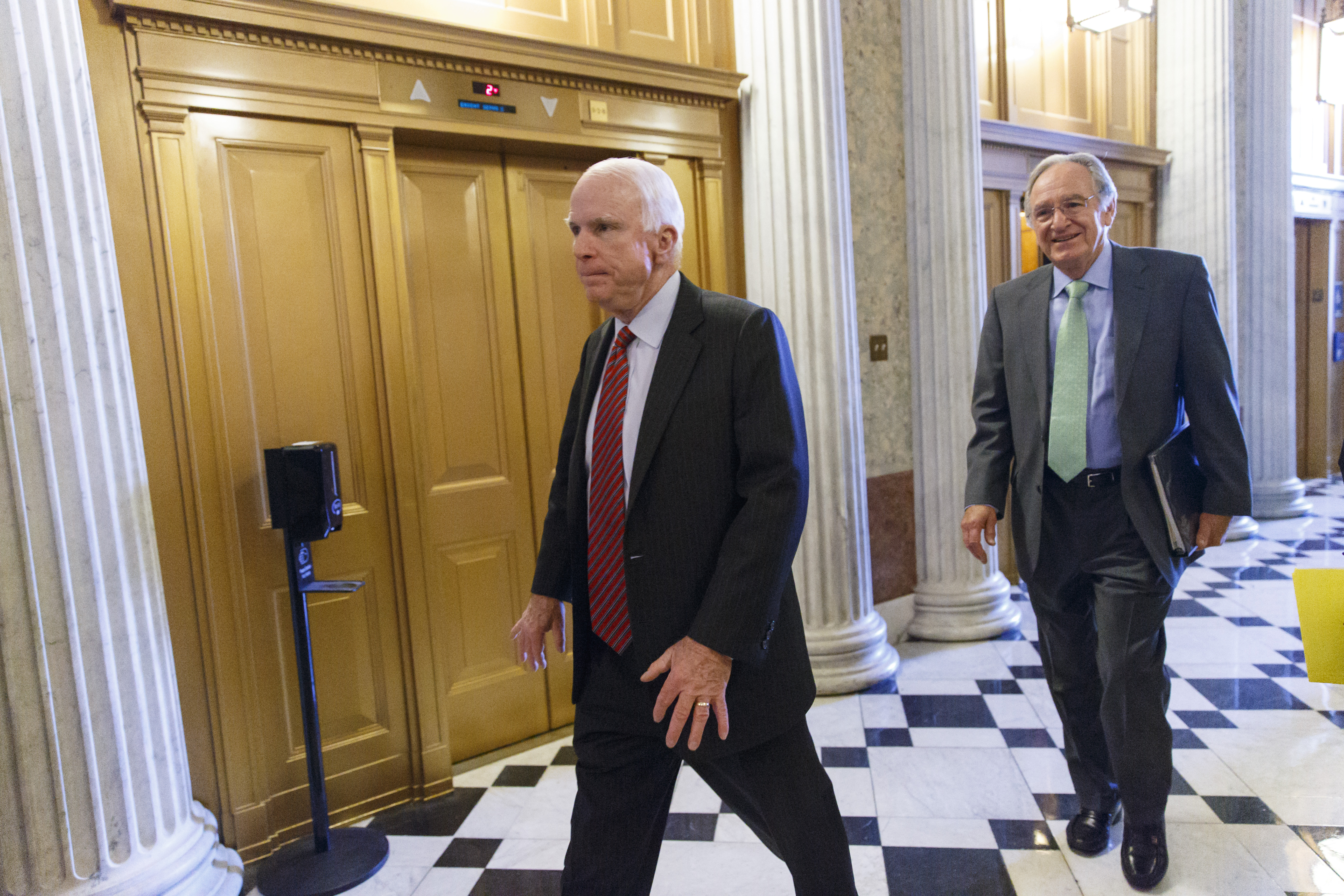 Sen. John McCain, R-Ariz., left, and Sen. Tom Harkin, D-Iowa, right, and other senators come and go from the chamber during votes at the Capitol in Washington, Tuesday, Feb. 25, 2014.