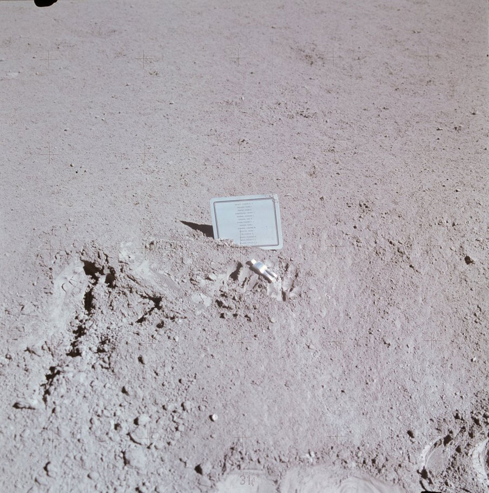 Dave Scott created a small memorial at the rover's final parking place to honor the astronauts and cosmonauts who had died prior to Apollo 15. The card lists the names. The figurine, Fallen Astronaut, was created by Belgian artist Paul van Hoeydonck. The imprints of Dave's fingers show up next to the figurine.