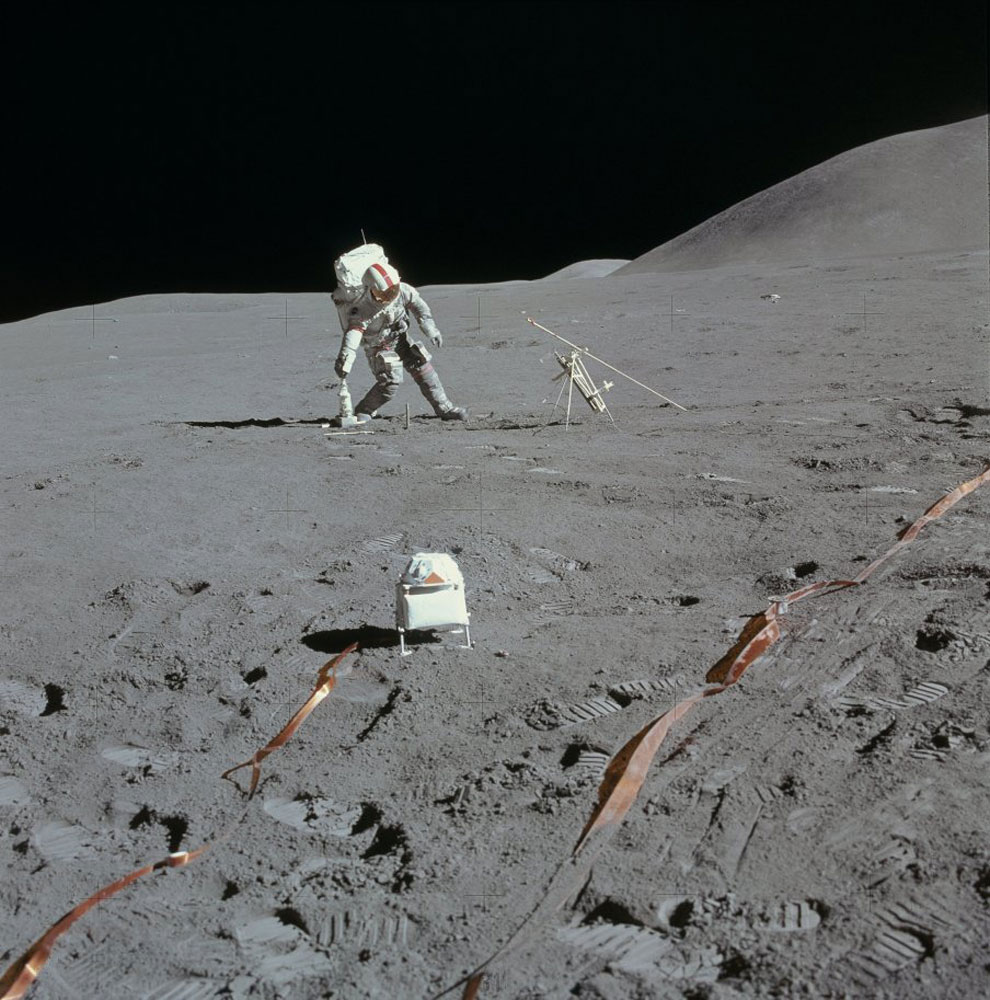 Scott, in the background, leans to his right to pick up his drill. The solar wind spectrometer is in the foreground.