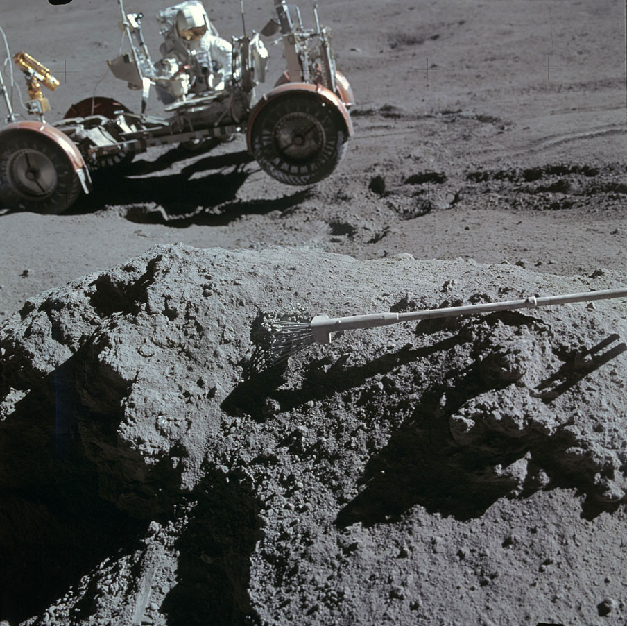 Scott rested his sample tongs atop a rock to photograph Irwin near the rover.  On the moon's irregular surface, at least one wheel—and sometimes two—were off the ground.
