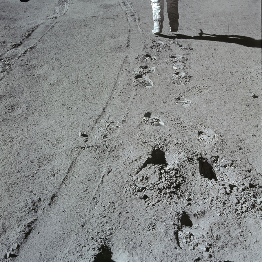 Apollo 15 was the first of three missions to include the lunar rover. Here, Irwin hikes ahead as Scott photographs him. Both footprints and wheel tracks are visible in the soil. They remain today.