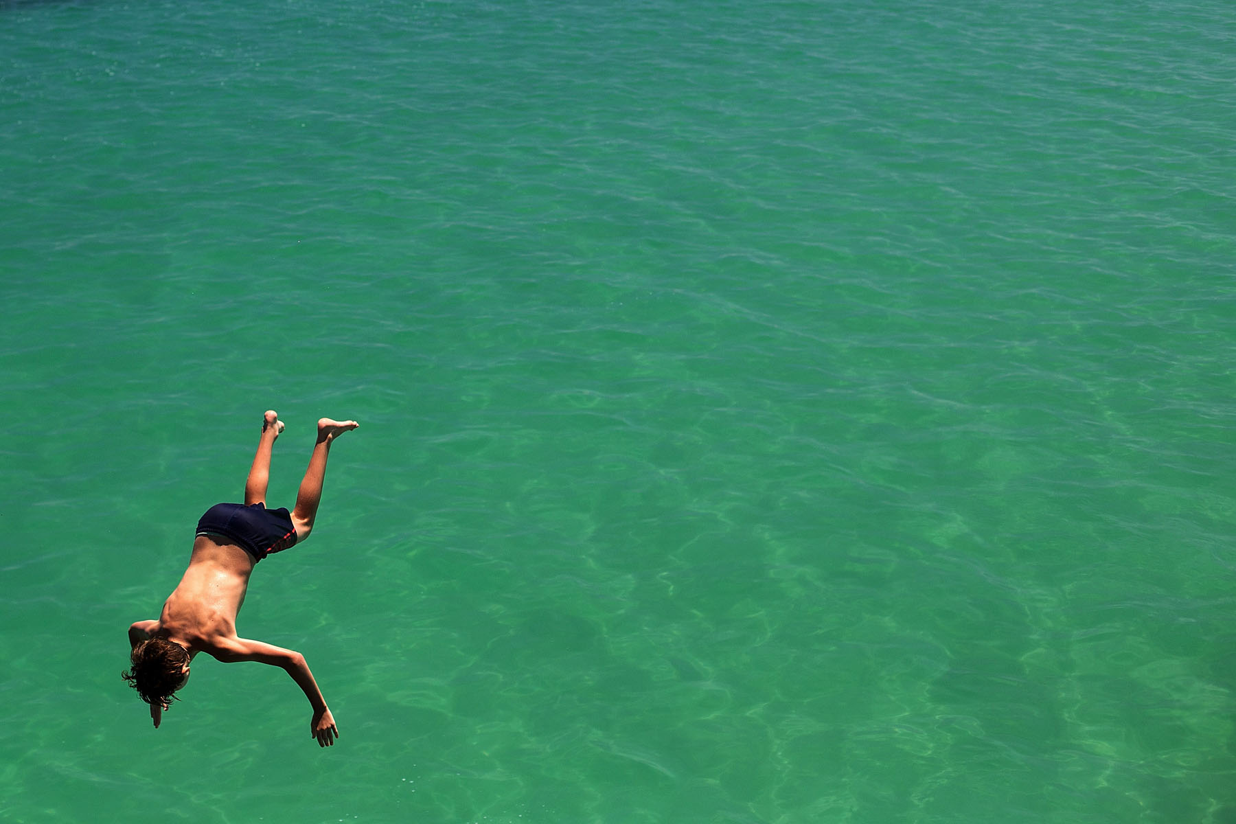 ADELAIDE, AUSTRALIA - JANUARY 13: A teenager jumps from the jetty during a heat wave at Glenelg beach on January 13, 2014 in Adelaide, Australia. Temperatures are expected to be over 40 degrees celsius all week with health authorities warning the young and elderly to remain indoors.  (Photo by Daniel Kalisz/Getty Images)