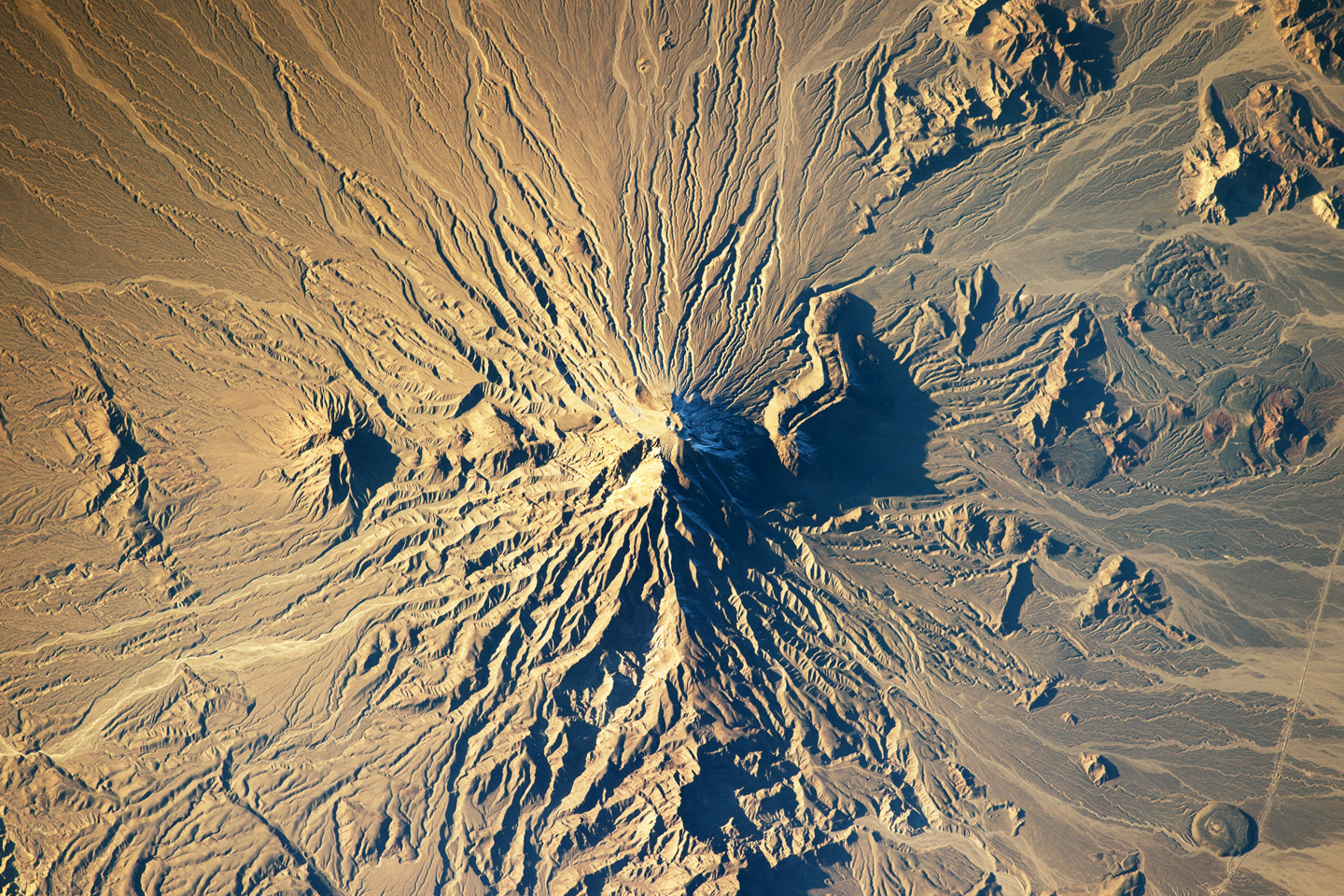 Bazman volcano is located in a remote region of southern Iran. While the volcano has the classic cone shape of a stratovolcano, it is also heavily dissected by channels that extend downwards from summit. This radial drainage pattern—similar to the spokes of a bicycle wheel—is readily observed from the International Space Station on Jan. 5, 2014.