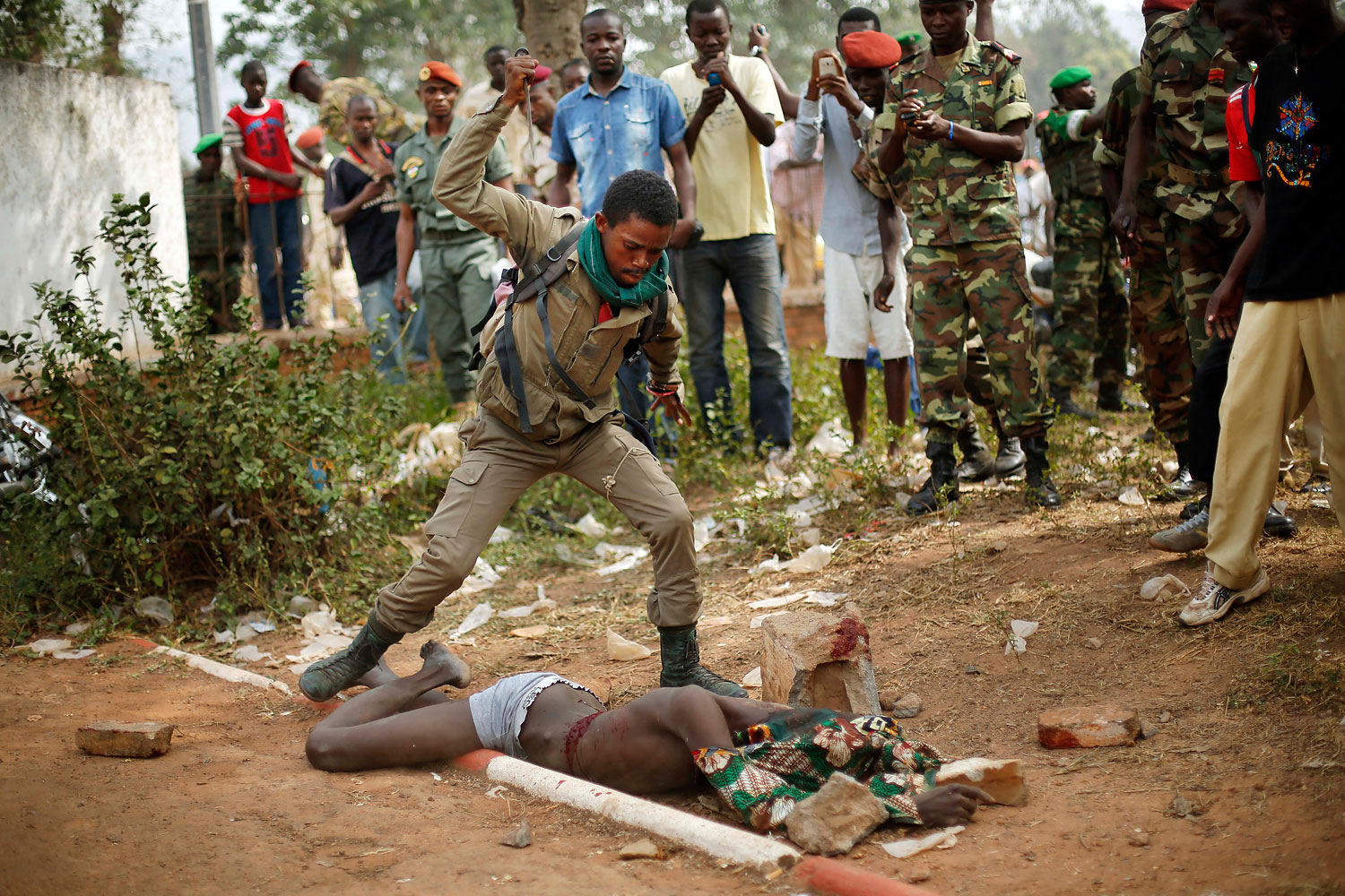 A newly enlisted Central African Armed Forces soldier stabs the lifeless body of a suspected Muslim Seleka militiaman moments after Central African Republic Interim President Catherine Samba-Panza addressed the troops in Bangui, Feb. 5, 2014.
