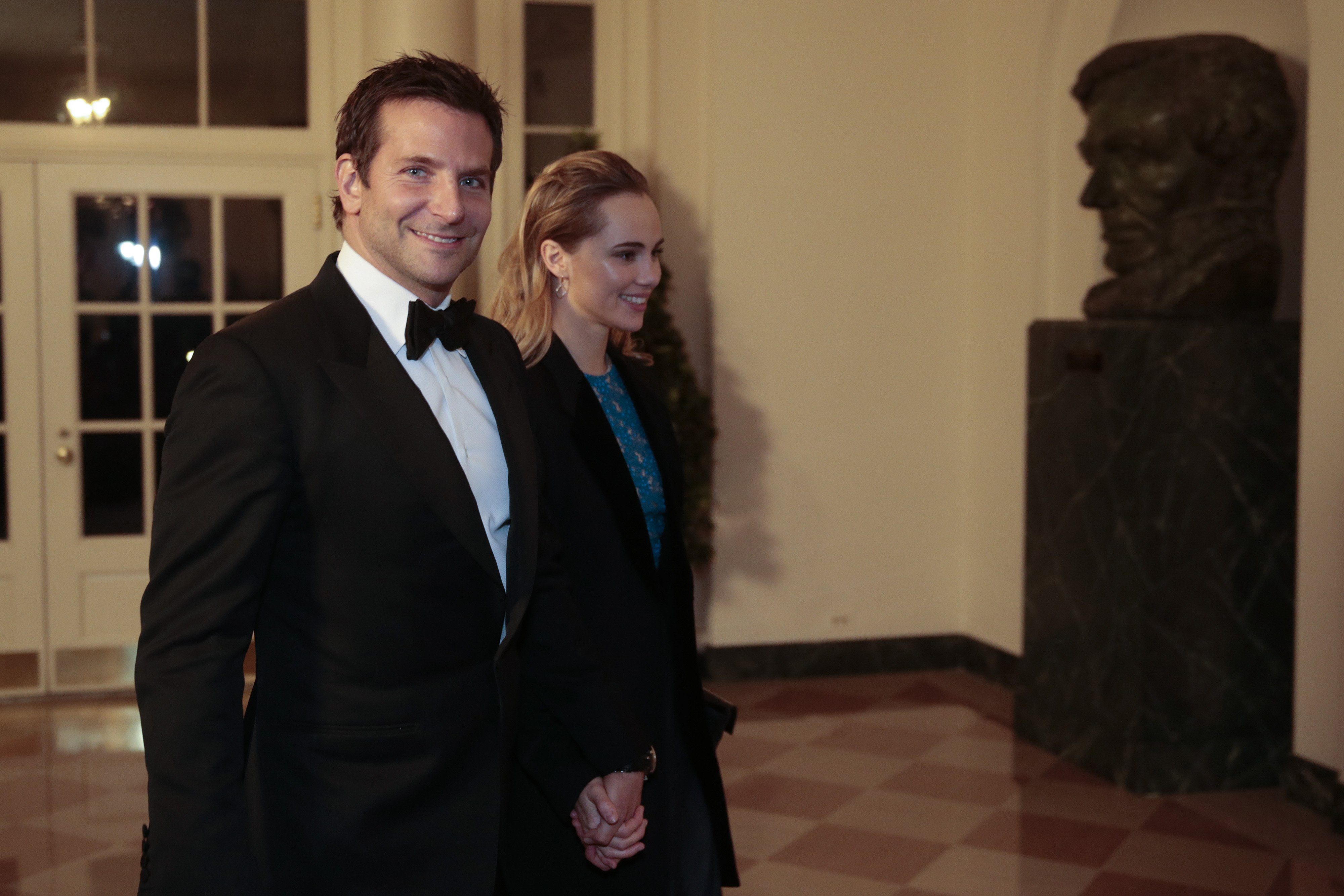 Actor Bradley Cooper, left, and Suki Waterhouse arrive to a state dinner hosted by U.S. President Barack Obama and U.S. first lady Michelle Obama in honor of French President Francois Hollande at the White House on February 11, 2014 in Washington.
