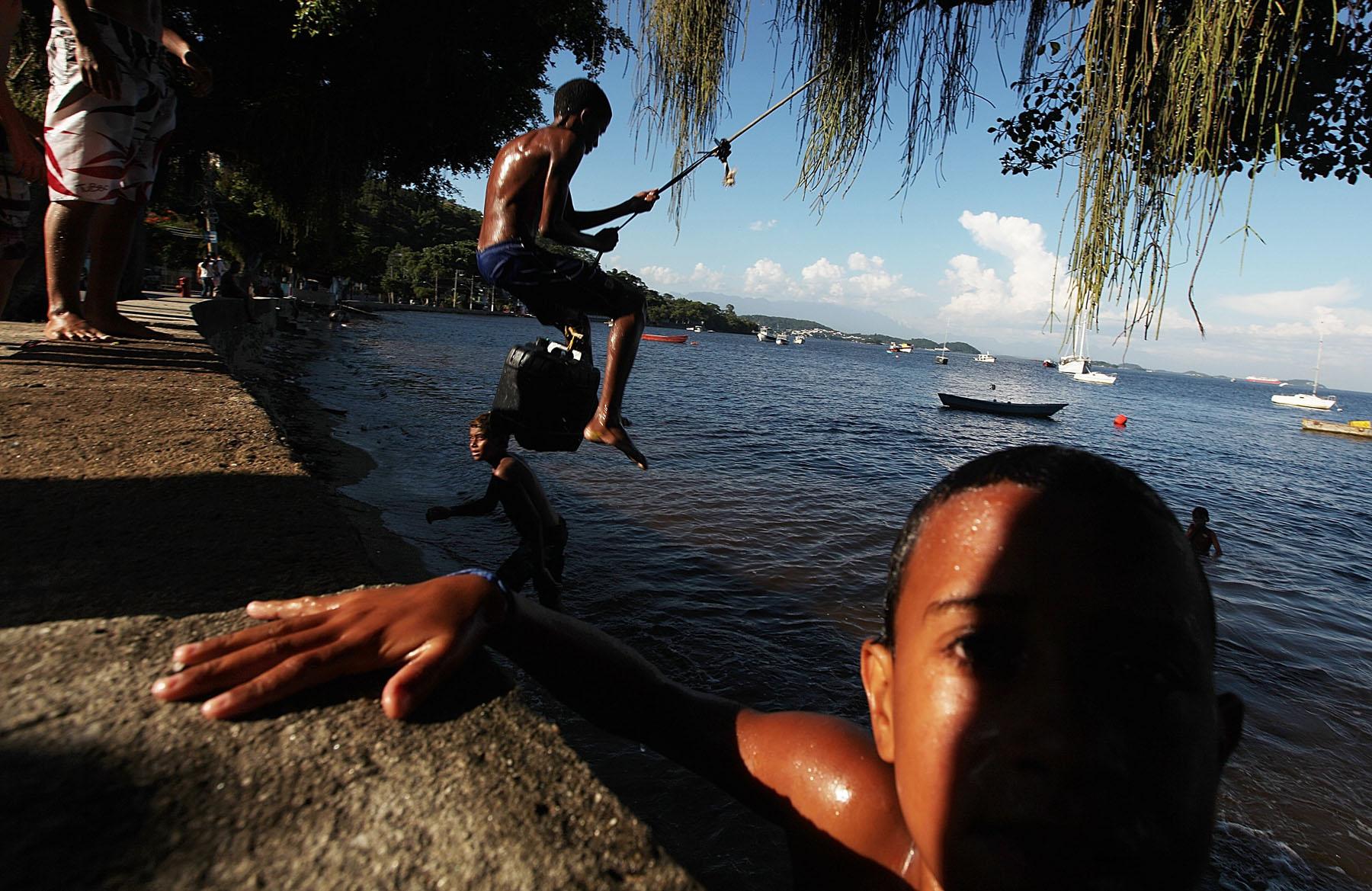 Kids play along the shoreline of Guanabara Bay in the Ilha do Governador neighborhood of Rio de Janeiro on Jan. 21, 2014.
