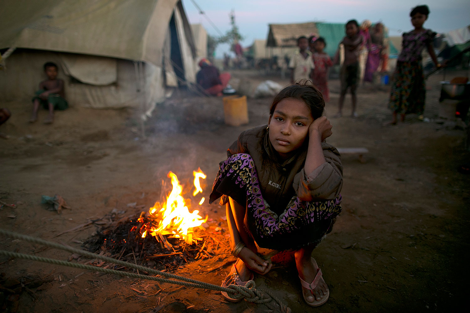A Rohingya woman sits by a fire at a crowded internally displaced persons (IDP) camp Nov. 23, 2012 on the outskirts of Sittwe, Burma