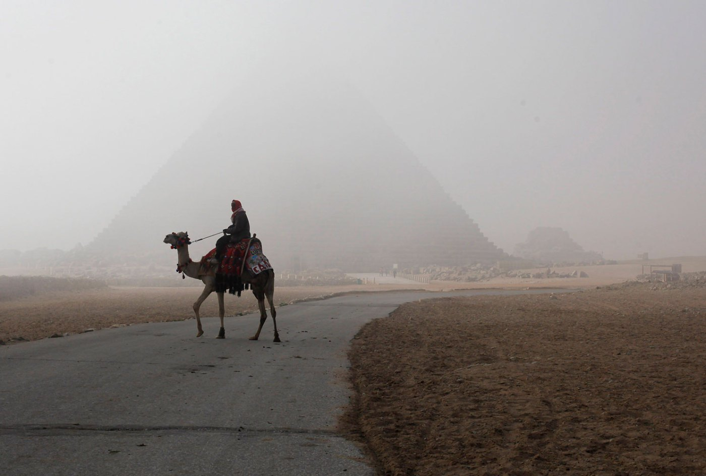 A man rides his camel as he waits for tourists at the Giza pyramids area, south of Cairo, Feb. 20, 2014.