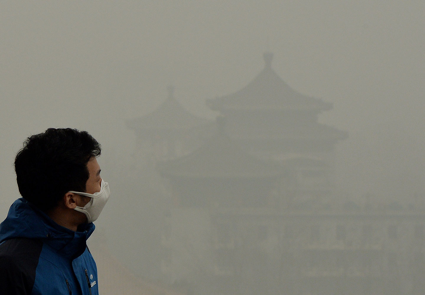 A tourist wearing a face mask climbs Jingshan Hill beside the Forbidden City as heavy air pollution continues to shroud Beijing on Feb. 26, 2014.