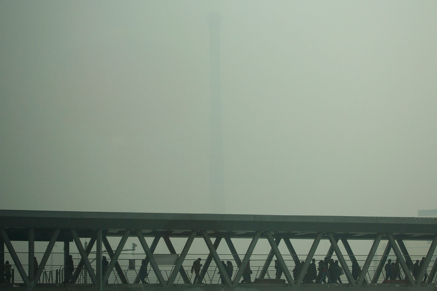 A chimney of a heating plant is obscured by heavy haze as commuters walk through a bridge linking a subway station and a bus station on a severely polluted day in Beijing, Feb. 25, 2014.