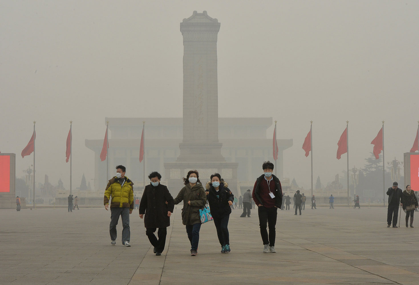 Chinese tourists wearing face masks visit Tiananmen Square as heavy air pollution continues to shroud Beijing on Feb. 26, 2014.