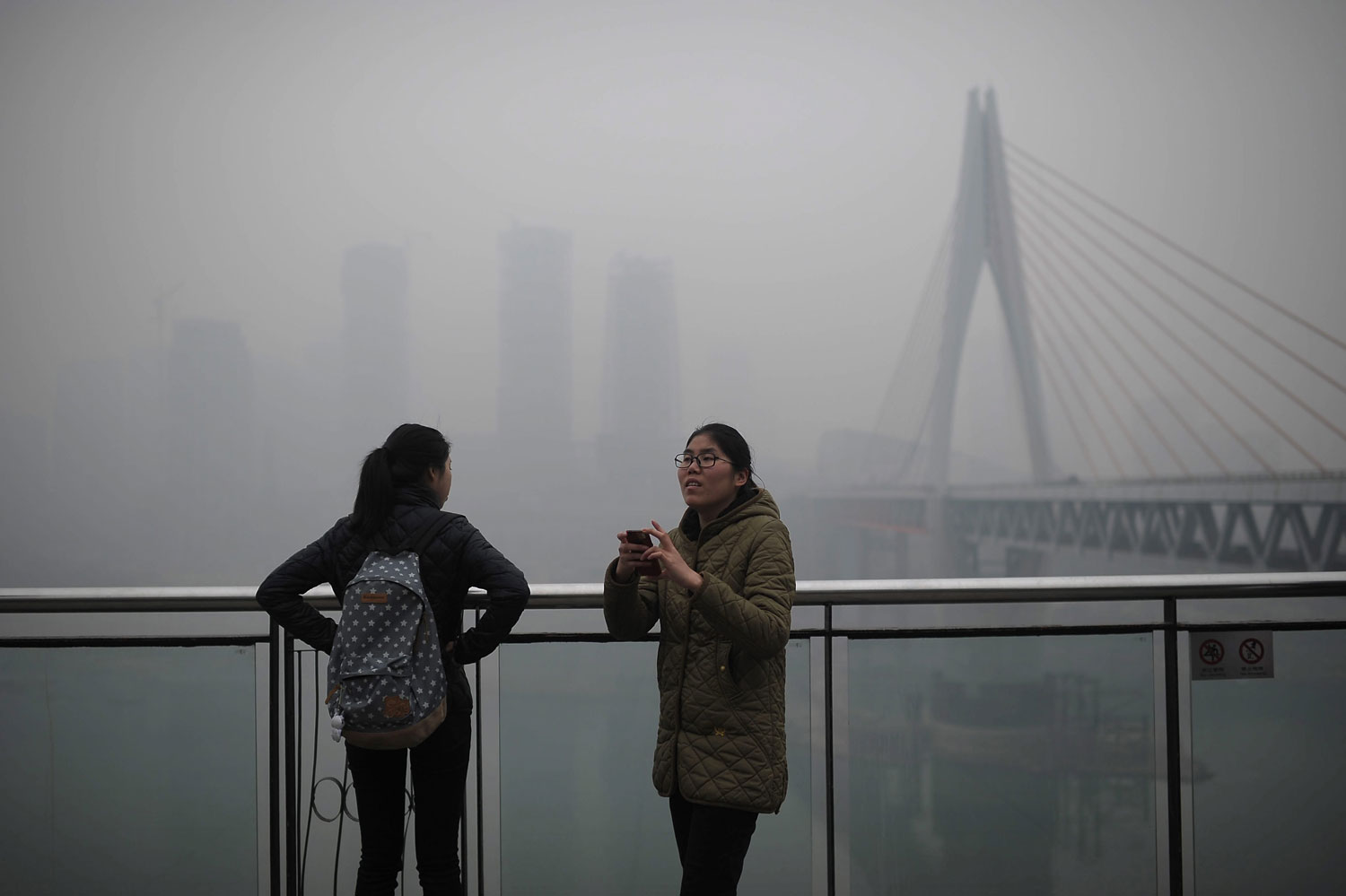 A woman tries to take photos on the river bank in the haze in southwest Chongqing Municipality, Feb. 23, 2014.