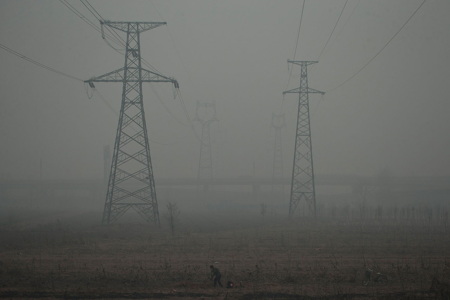 A farmer shovels in a field near electric pylons in heavy haze on a severely polluted day in Shijiazhuang, in northern China's Hebei province, Feb. 26, 2014.