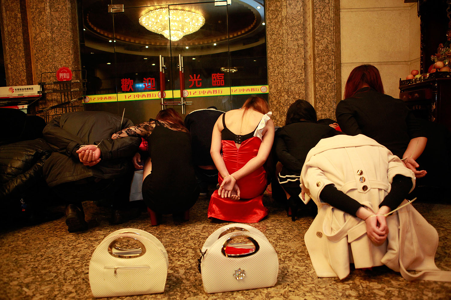 This picture taken late on Feb. 9, 2014 shows alleged sex workers and clients detained by Chinese police after a raid on an entertainment center in Dongguan, southern China's Guangdong province