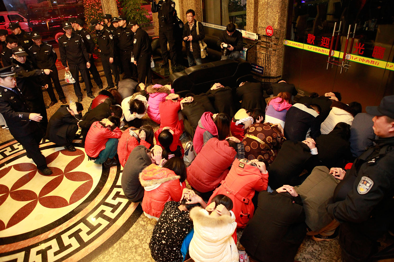 Chinese police rounding up alleged sex workers and clients at an entertainment center in Dongguan, in southern China's Guangdong province, on Feb. 9, 2014