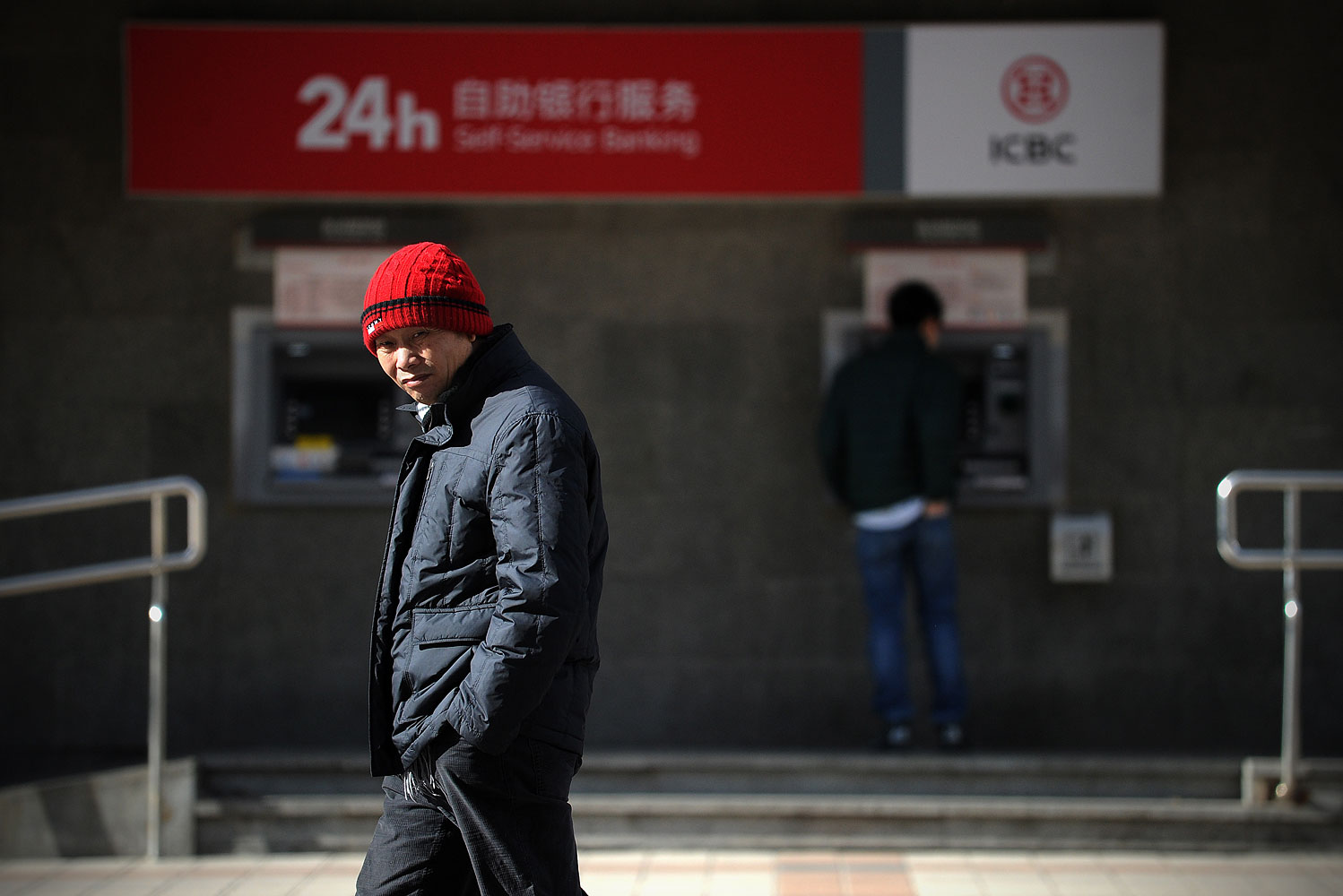 A man walking past a ATM machine at the entrance of a bank in Beijing, Jan. 25, 2014