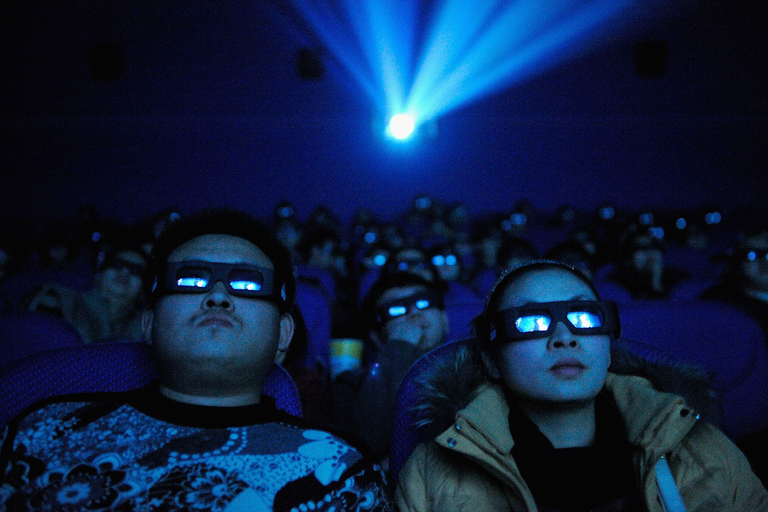A Chinese cinema audience watches a movie through 3D glasses