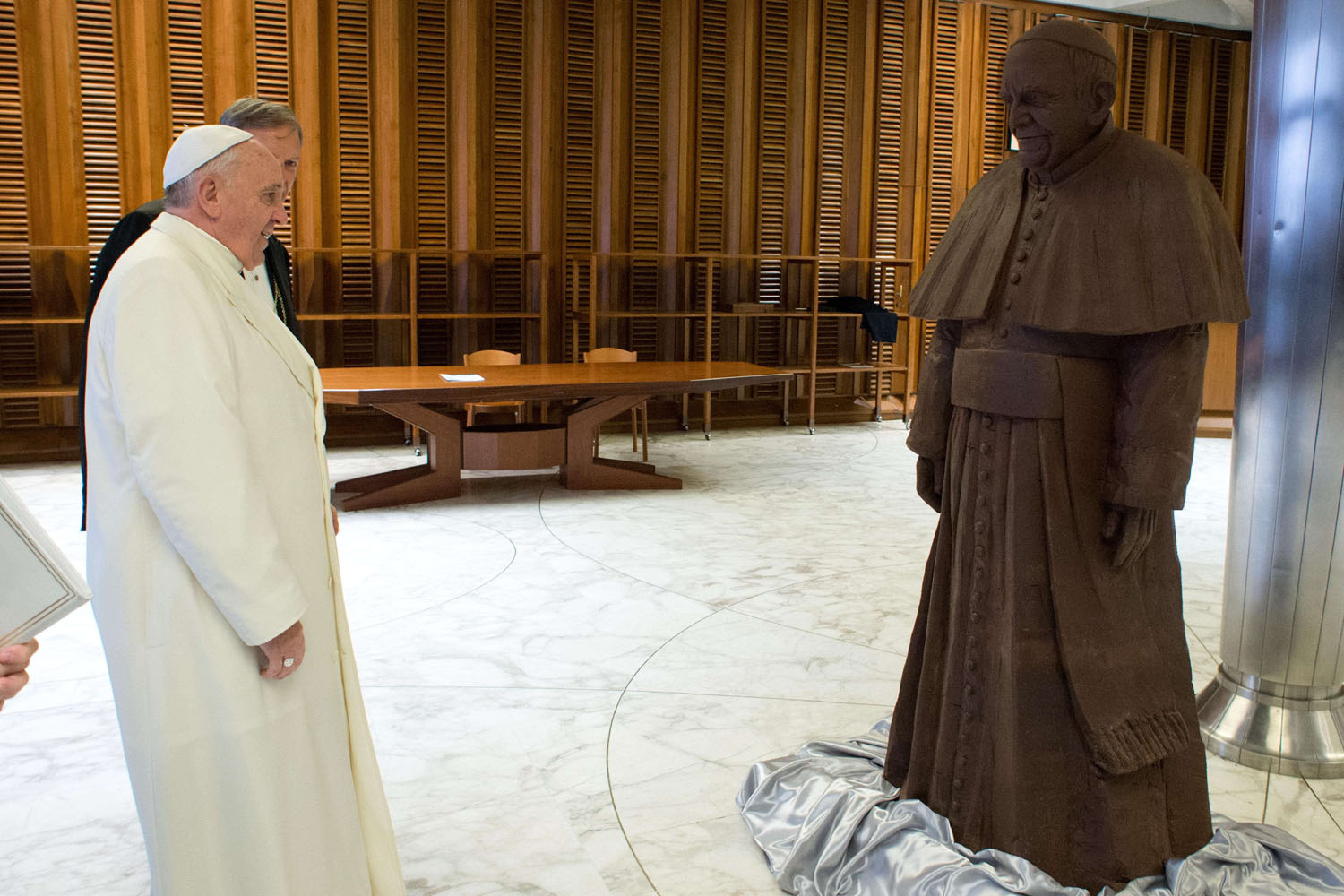 Pope Francis looks at a chocolate statue of himself, given to him after his weekly audience, on Feb. 5, 2014.