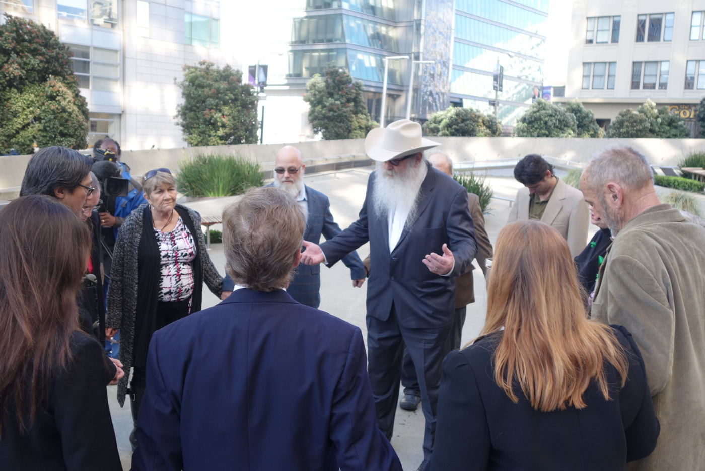 Bryan Davies, owner of medical marijuana dispensary Canna Care, leads supporters in prayer before facing the Internal Revenue Service in tax court on Feb. 24, 2014.