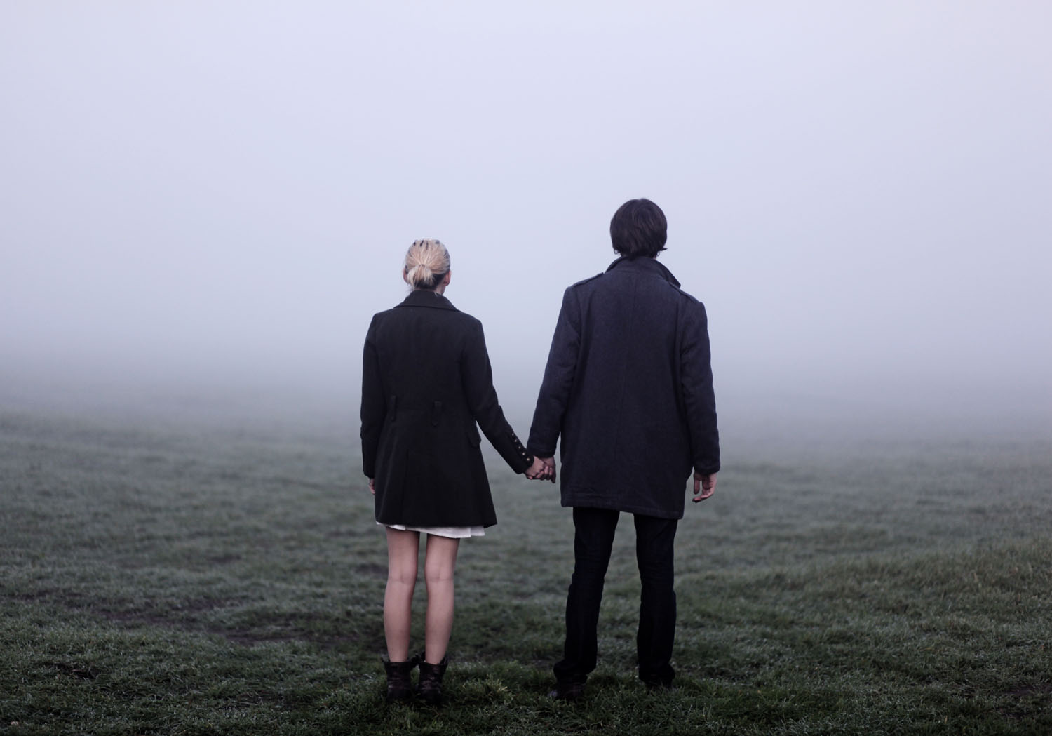 Couple holding hands outside in thick fog.